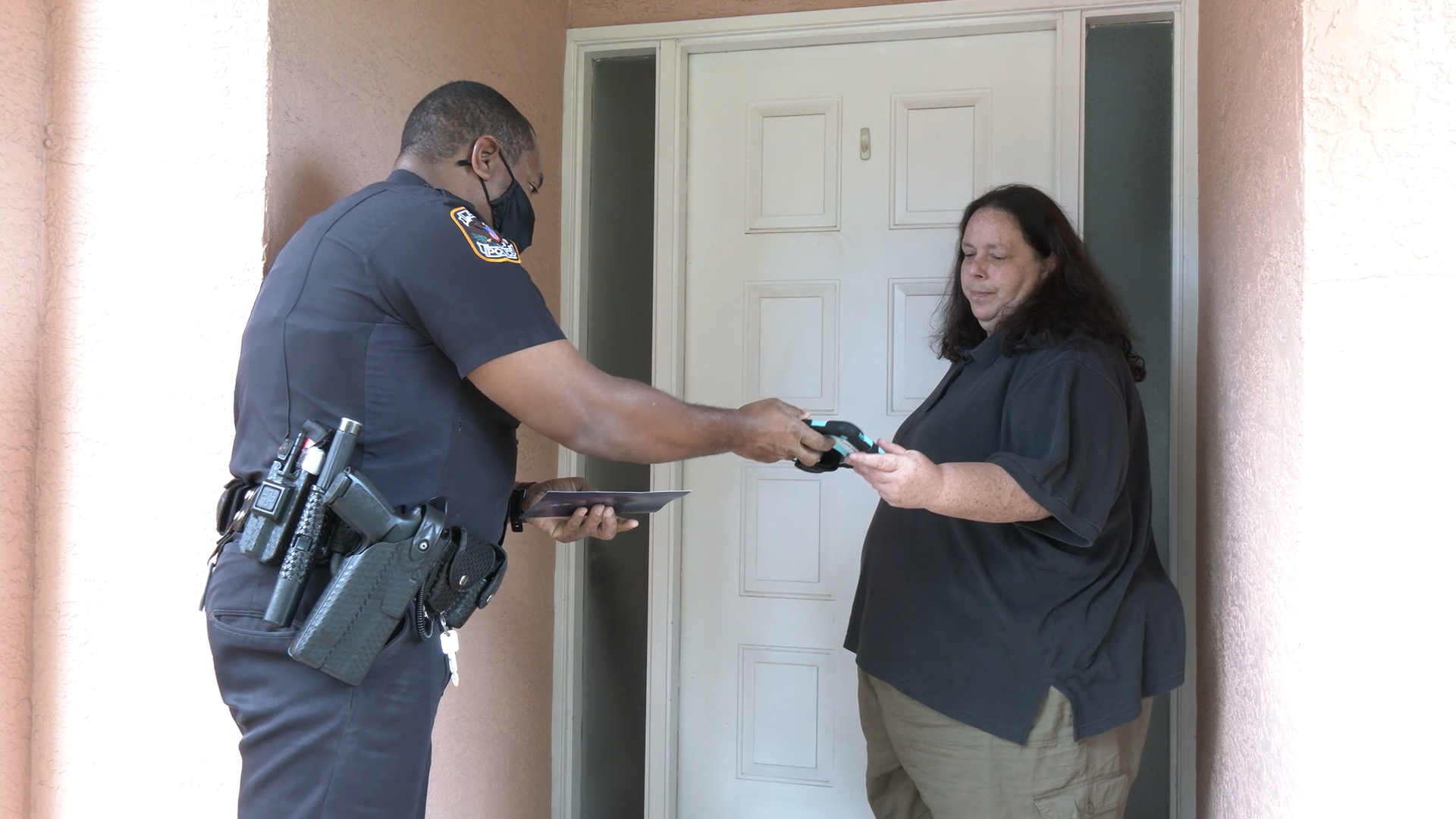 A police officer hands a tablet to a woman