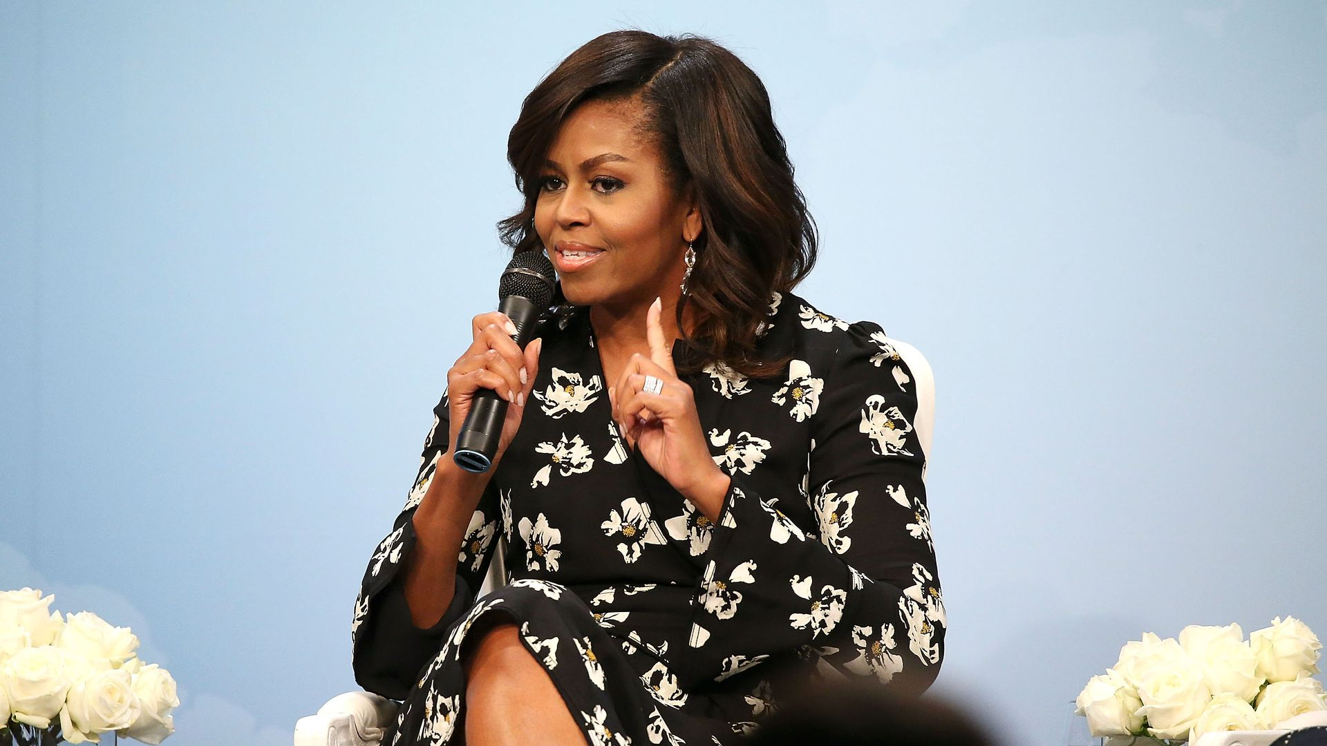 In this image, Michelle Obama sits and speaks into a microphone.