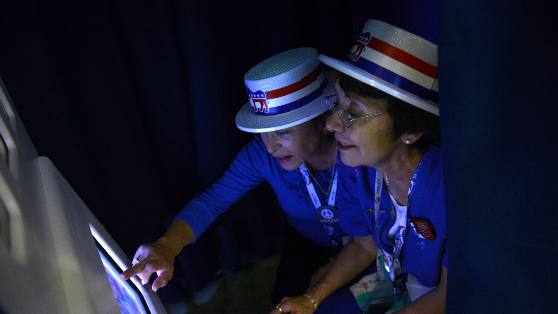 Two women in democratic red white blue hats touch a touch screen