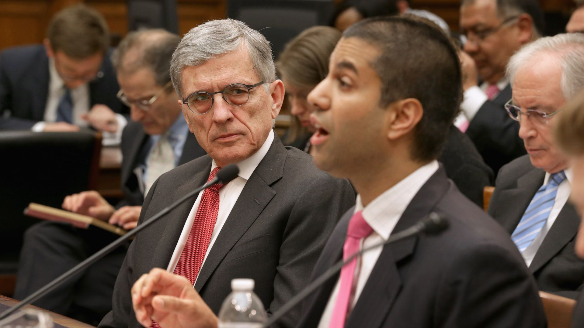 Tom Wheeler looks at Ajit Pai while they both testify