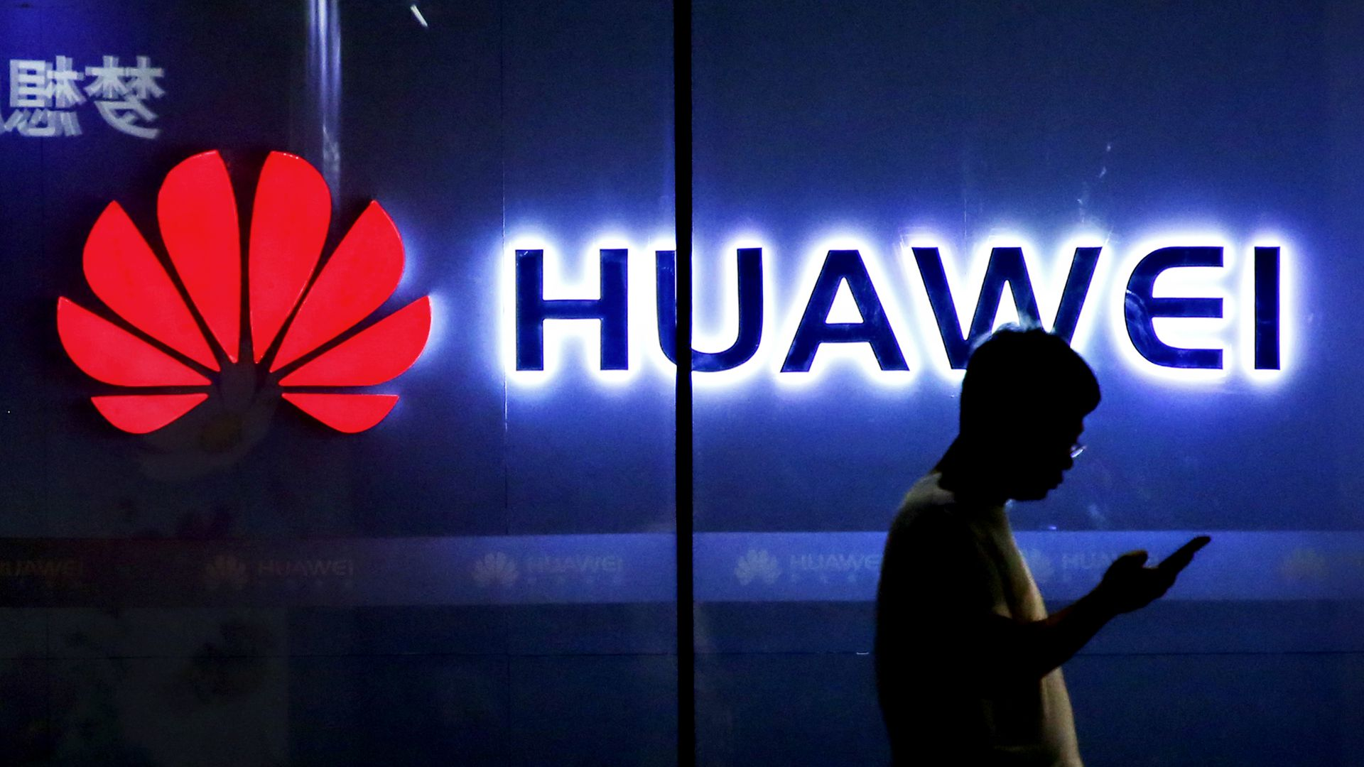 Photo of a man with a smartphone silhouetted against a glowing Huawei sign