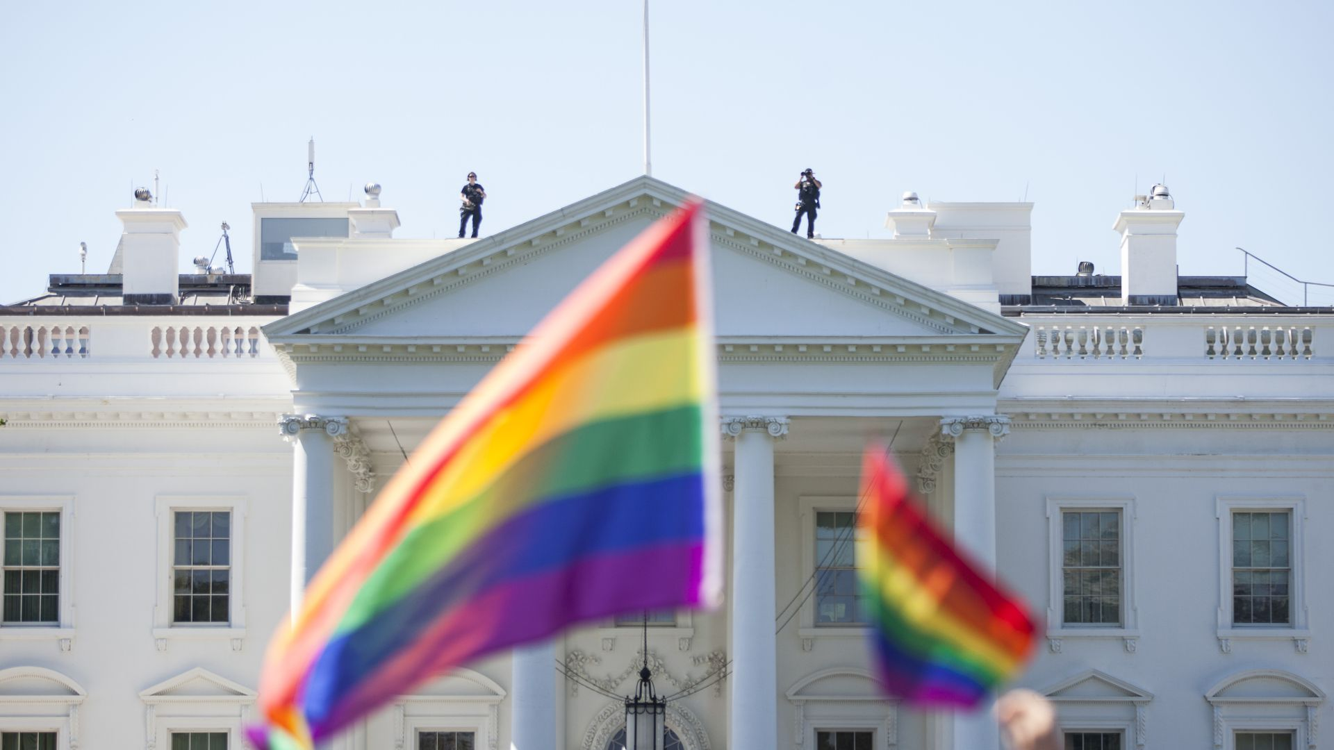 Rainbow flags in the foreground of a shot of the White House' south lawn