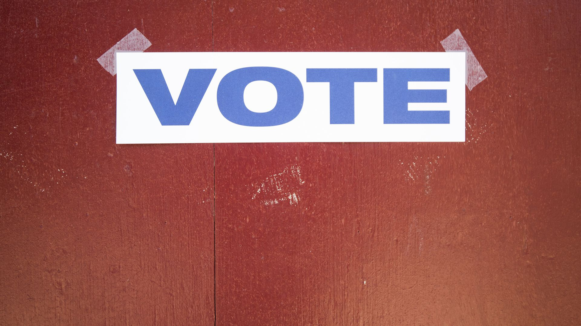"A ""Vote"" sign taped to a door."