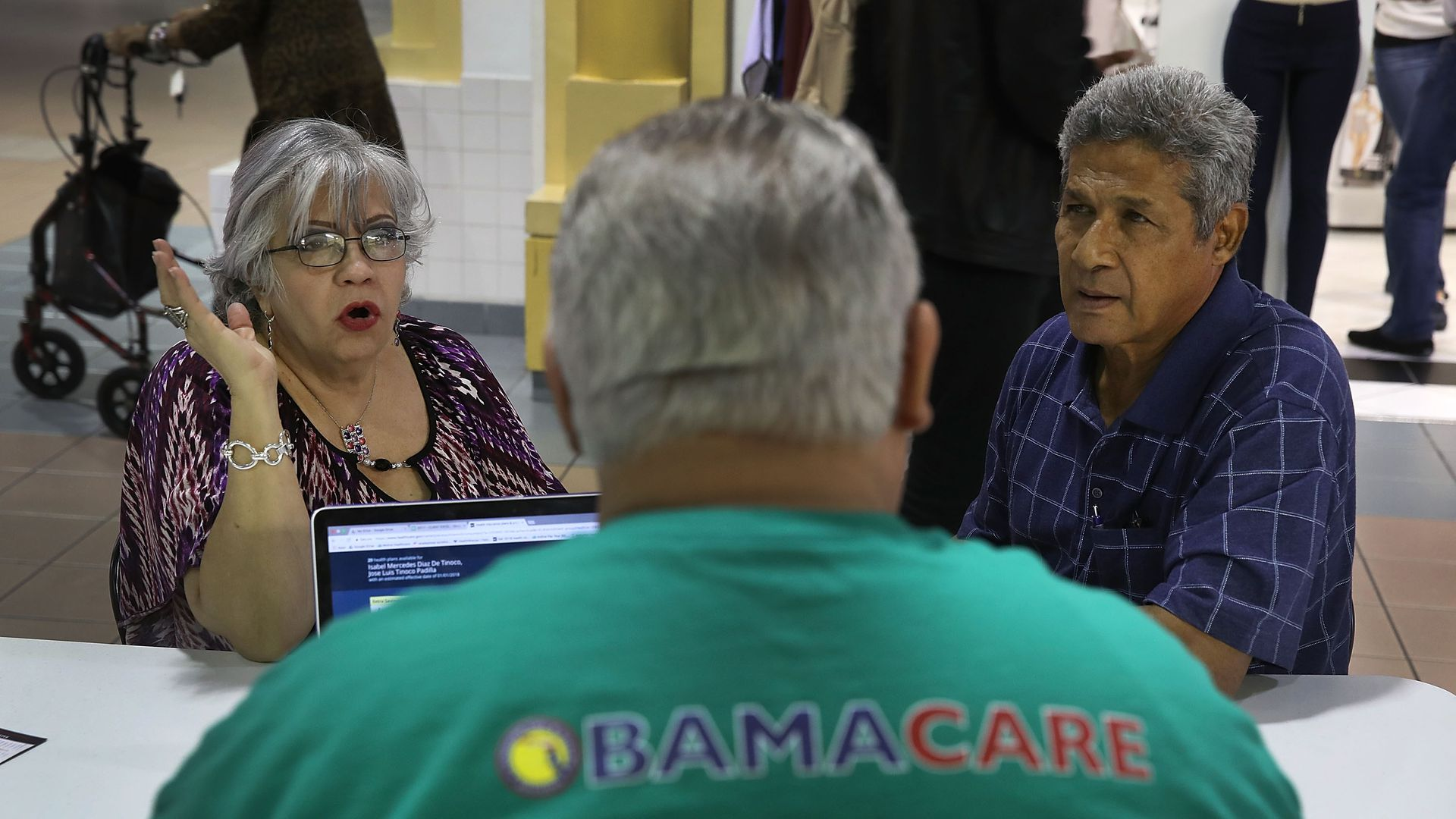 A man helping people sign up for coverage under the Affordable Care Act