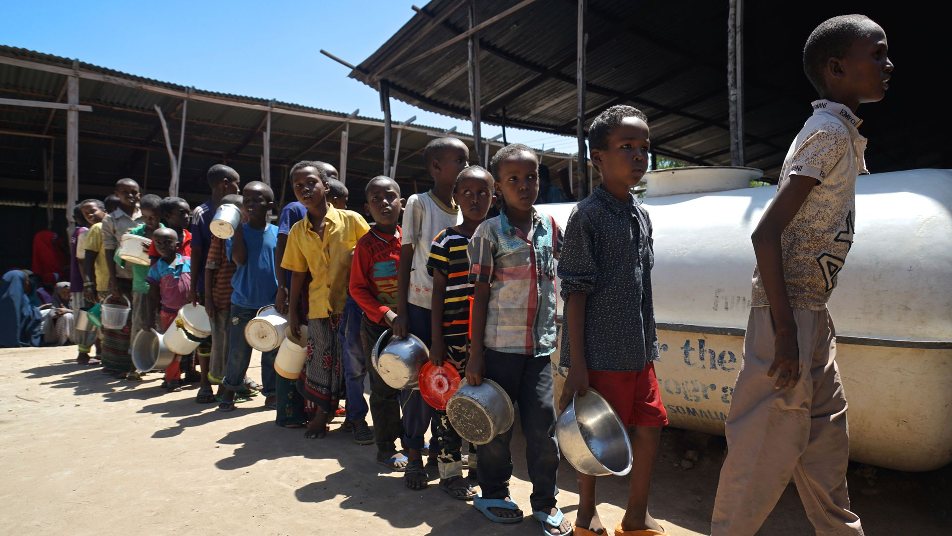 Young Somali boys stand in line carrying metal dishes