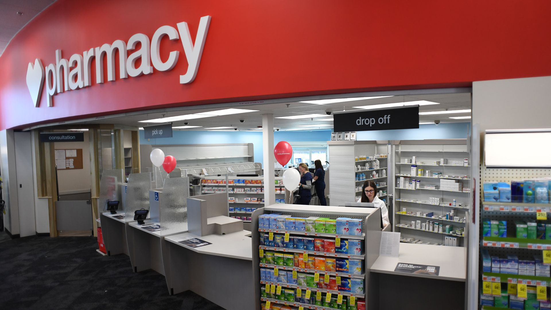 A CVS pharmacist stands behind the counter.