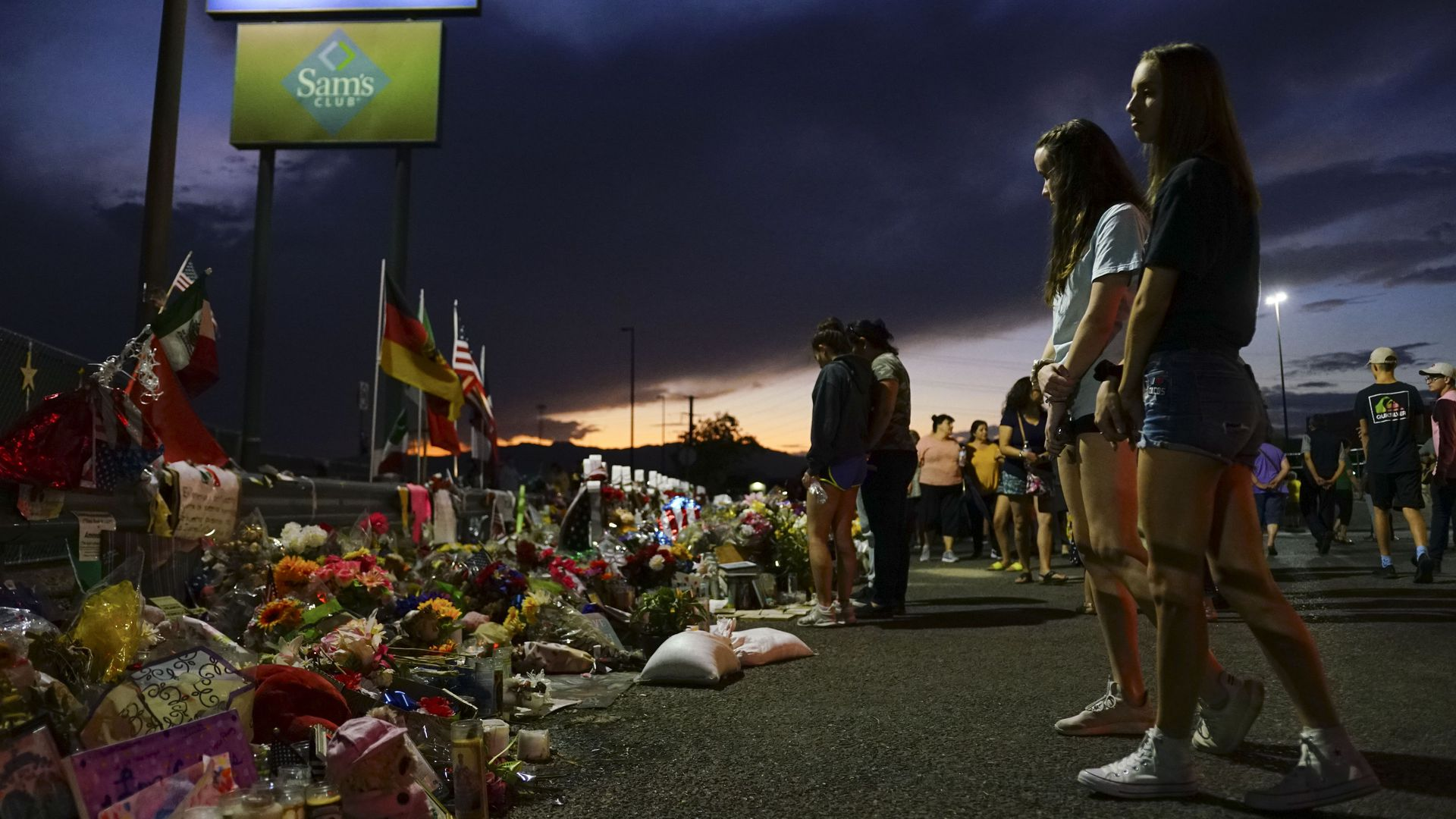 People look at flowers laid out to honor the victims of the El Paso shooting.