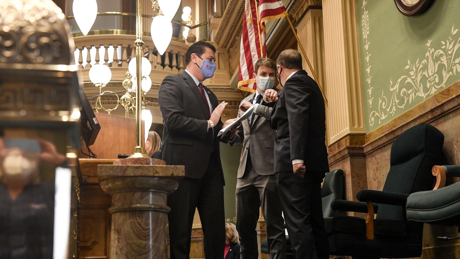 Colorado Gov. Jared Polis elbow bumps State House Speaker Alec Garnett ahead of a joint address.