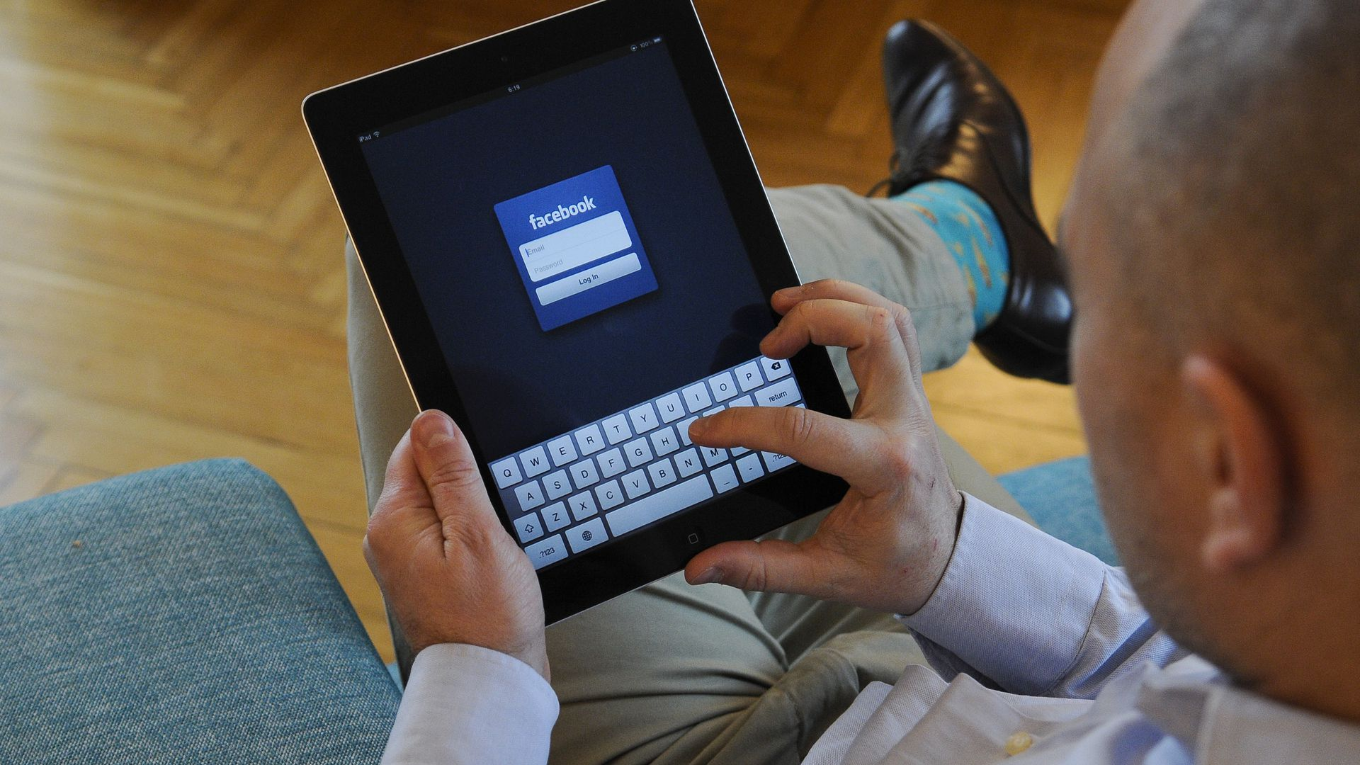 A man is seen holding an iPad with Facebook login screen.