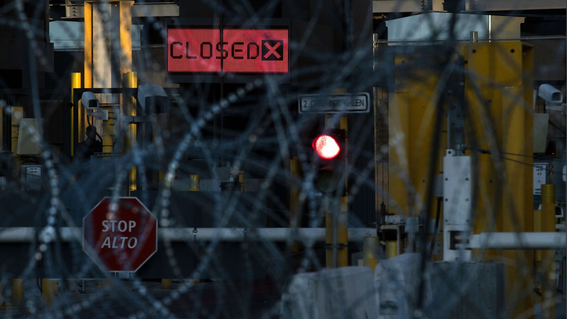 "A photo through barbed wire of a port of entry with a ""closed"" sign"