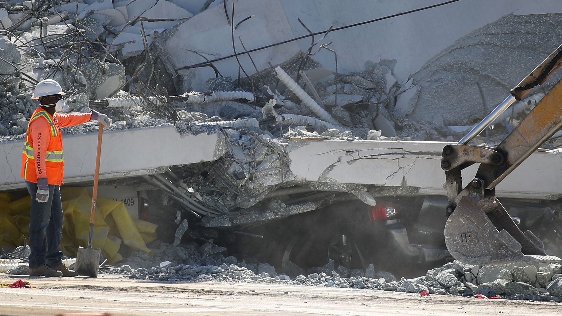 A crushed vehicle is seen near a worker as law enforcement and members of the National Transportation Safety Board investigate the scene where a pedestrian bridge collapsed