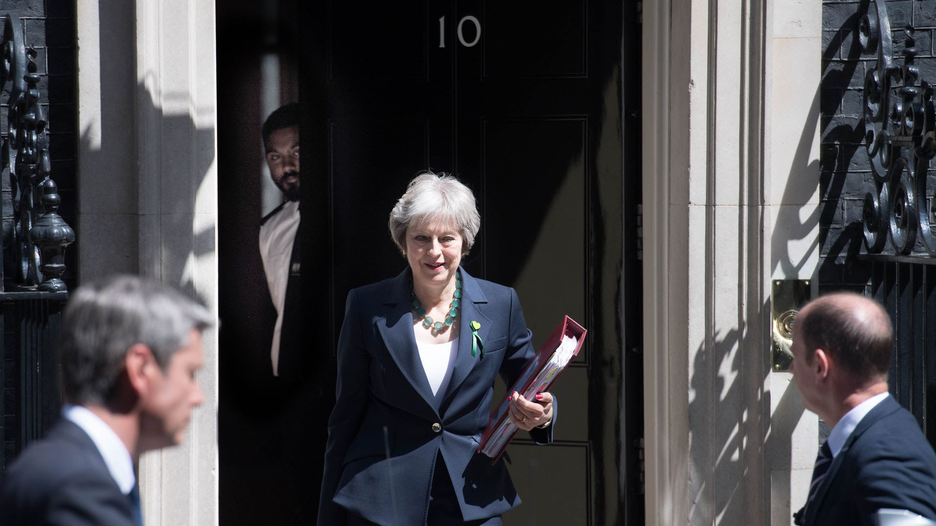 Theresa May walks down the stairs outside Number 10 in England