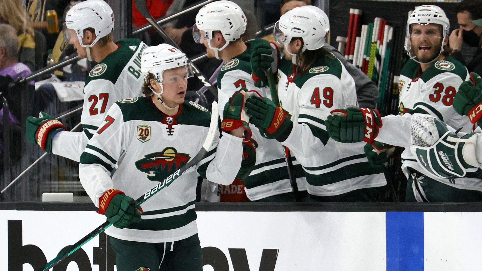 Minnesota Wild players high five on the ice.