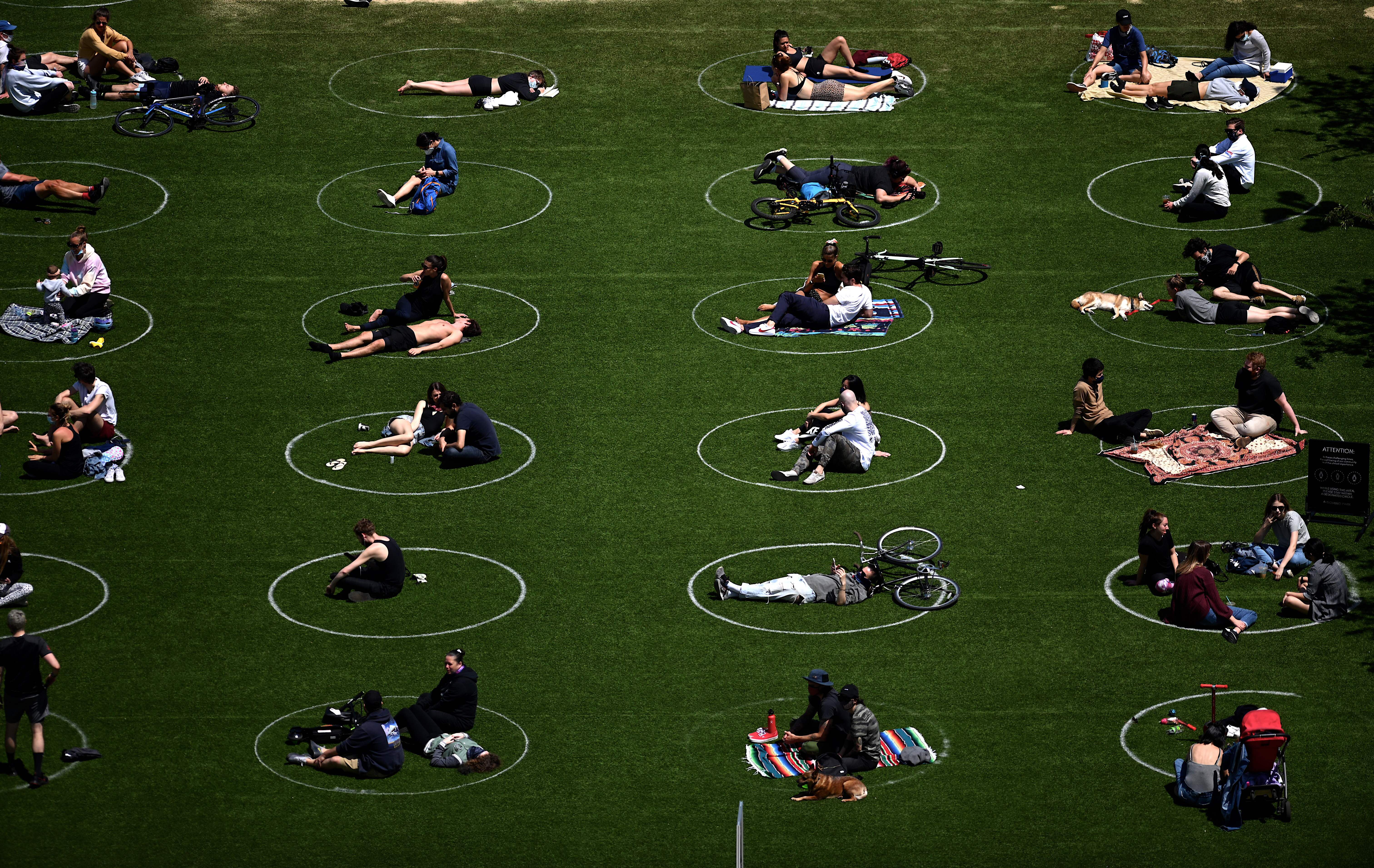 People are seen practising social distancing in white circles in Domino Park, during the Covid-19 pandemic on May 17, 2020 the in Brooklyn borough of New York City.