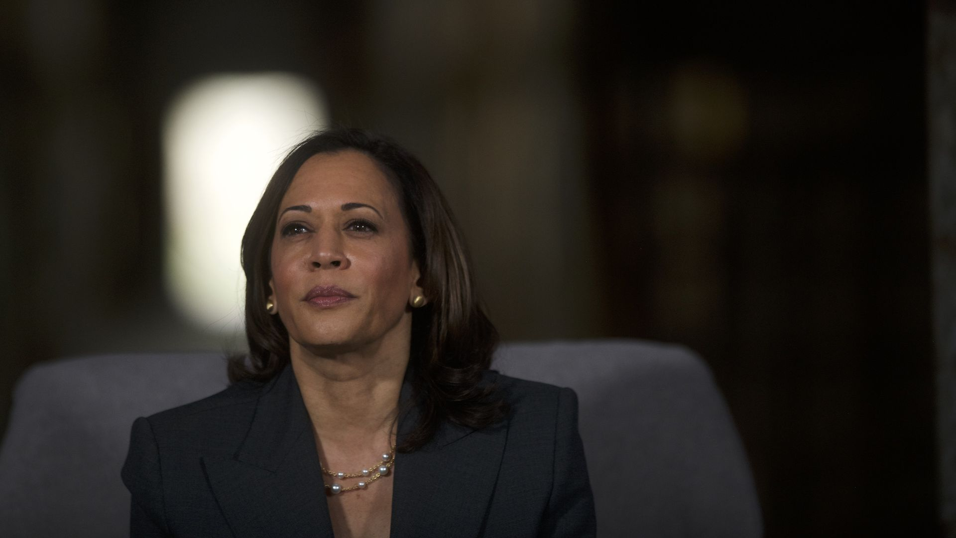 In this image, Kamala Harris sits and looks to the left