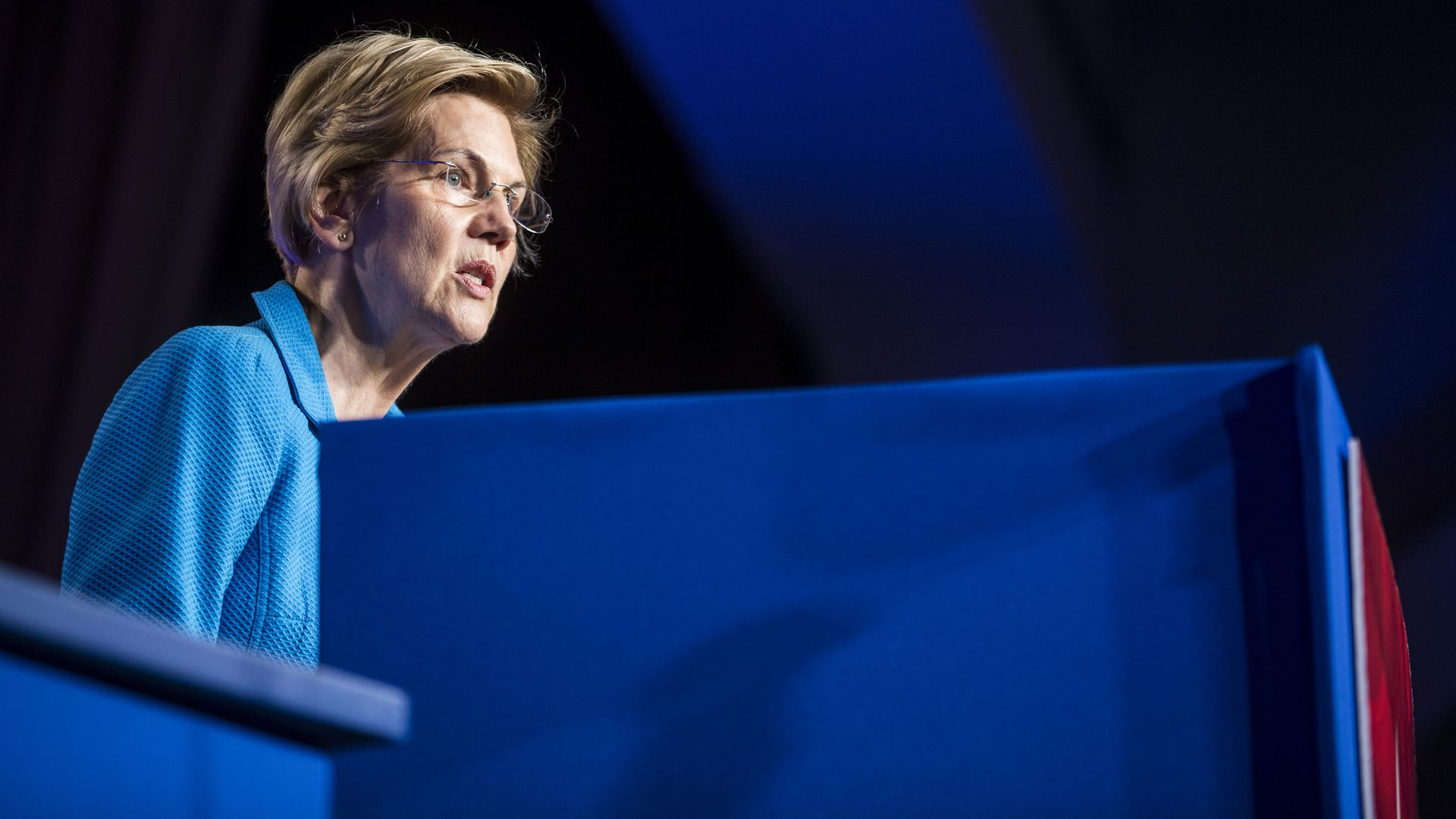 In this image, Elizabeth Warren stands and speaks behind a blue podium.