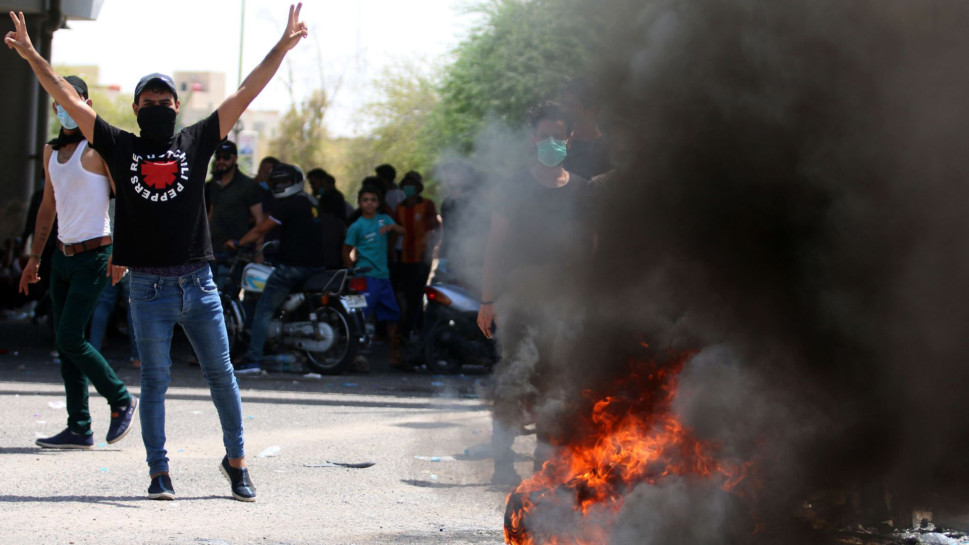 A protestor stands next to a burning tire, with his hands raised gesturing the peace sign.