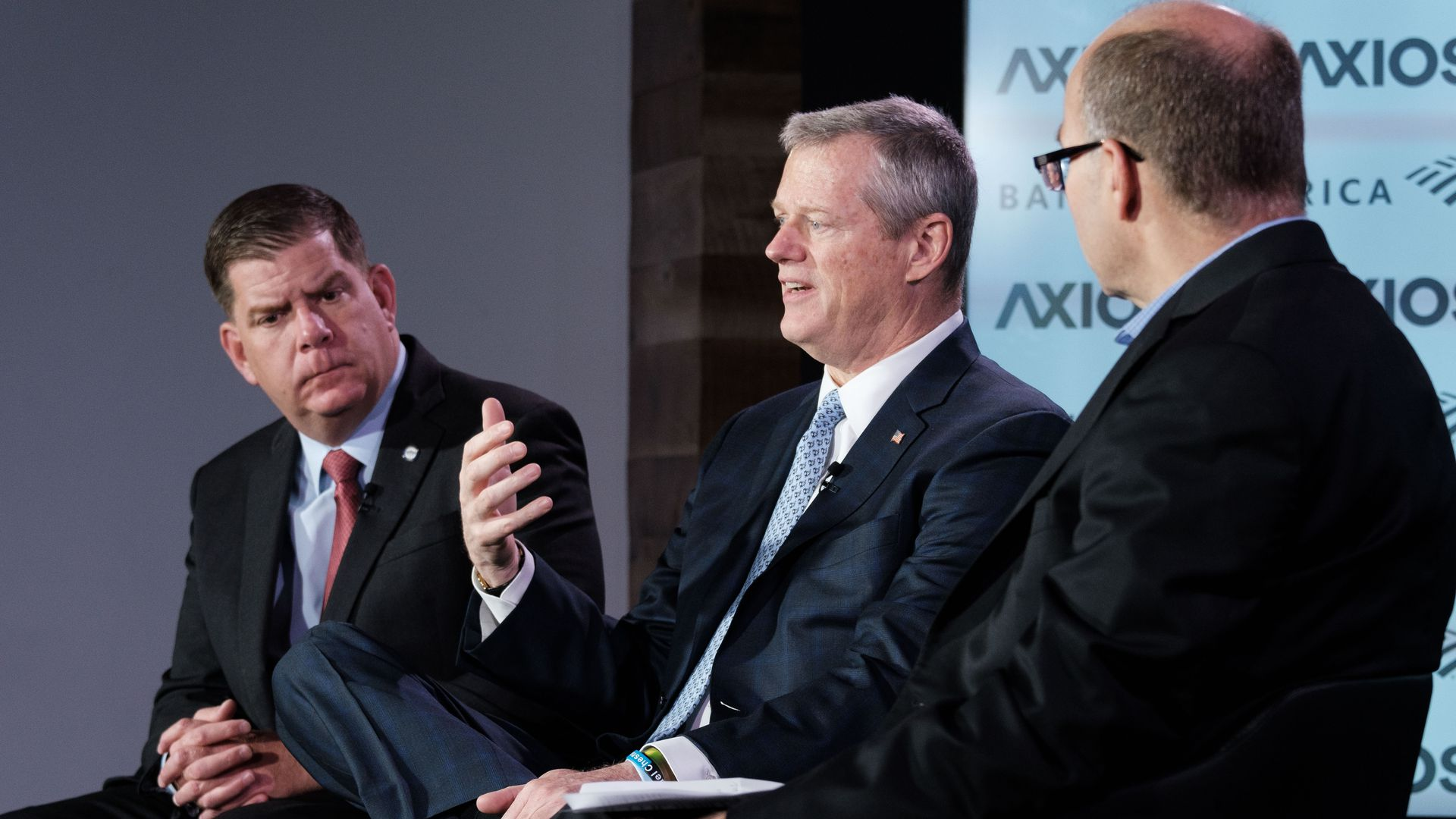 Three men sit on Axios stage for event.