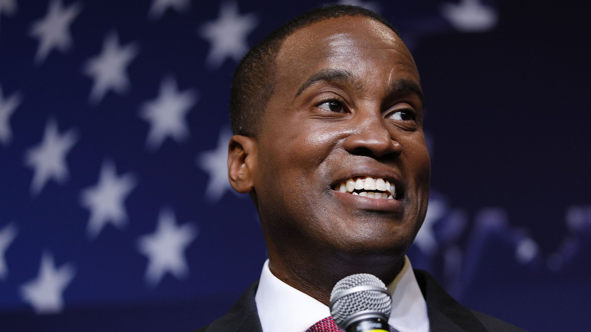 John James holding a microphone with an American flag in the background.