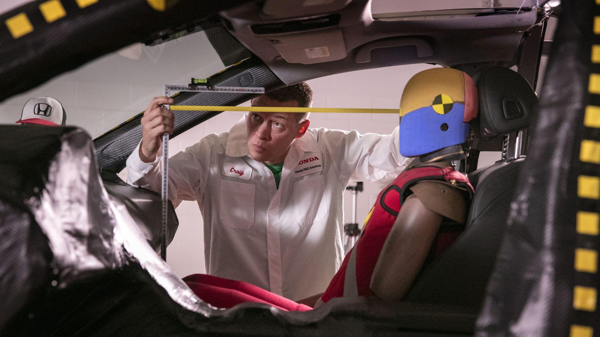 Honda engineer takes measurements ahead of a simulated crash test