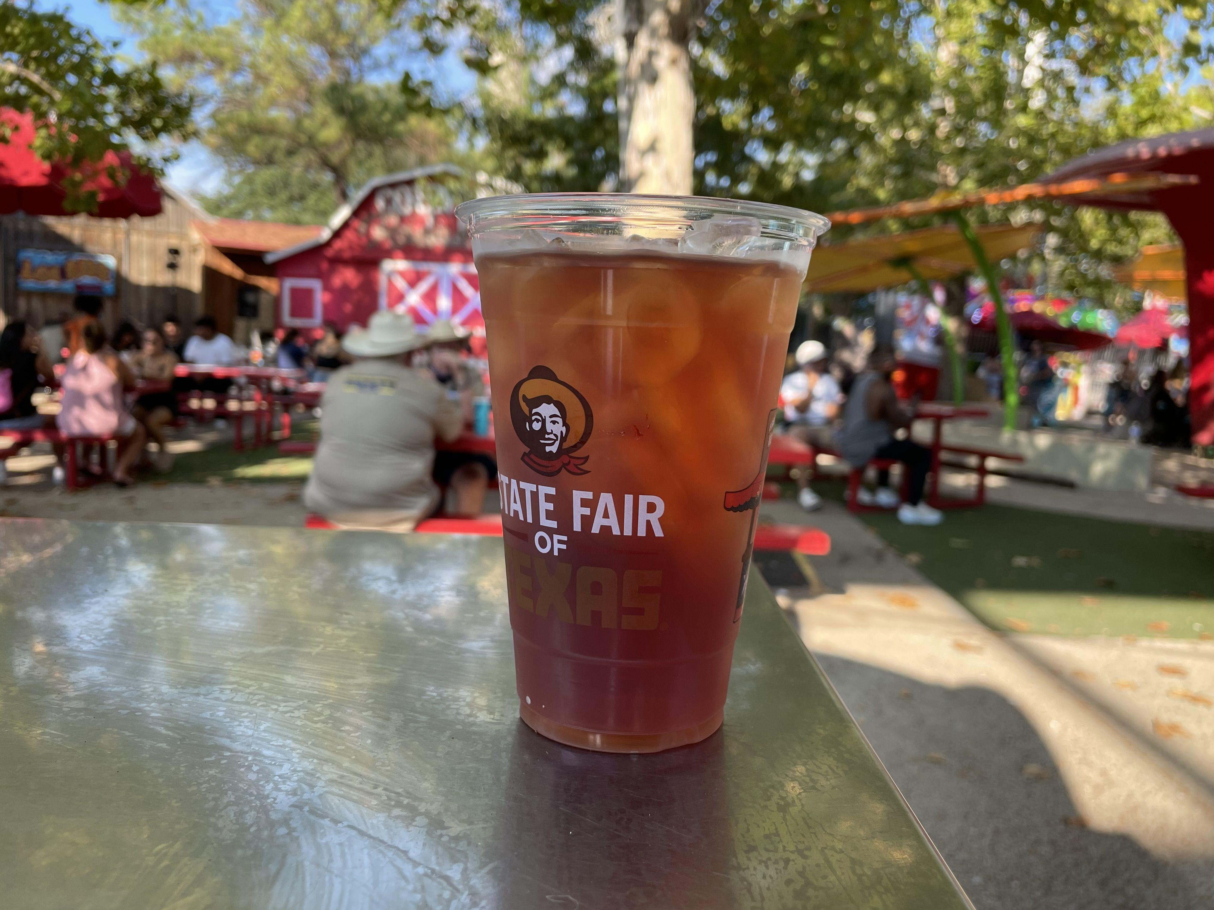 A cold iced tea in a plastic cup in an outdoor setting