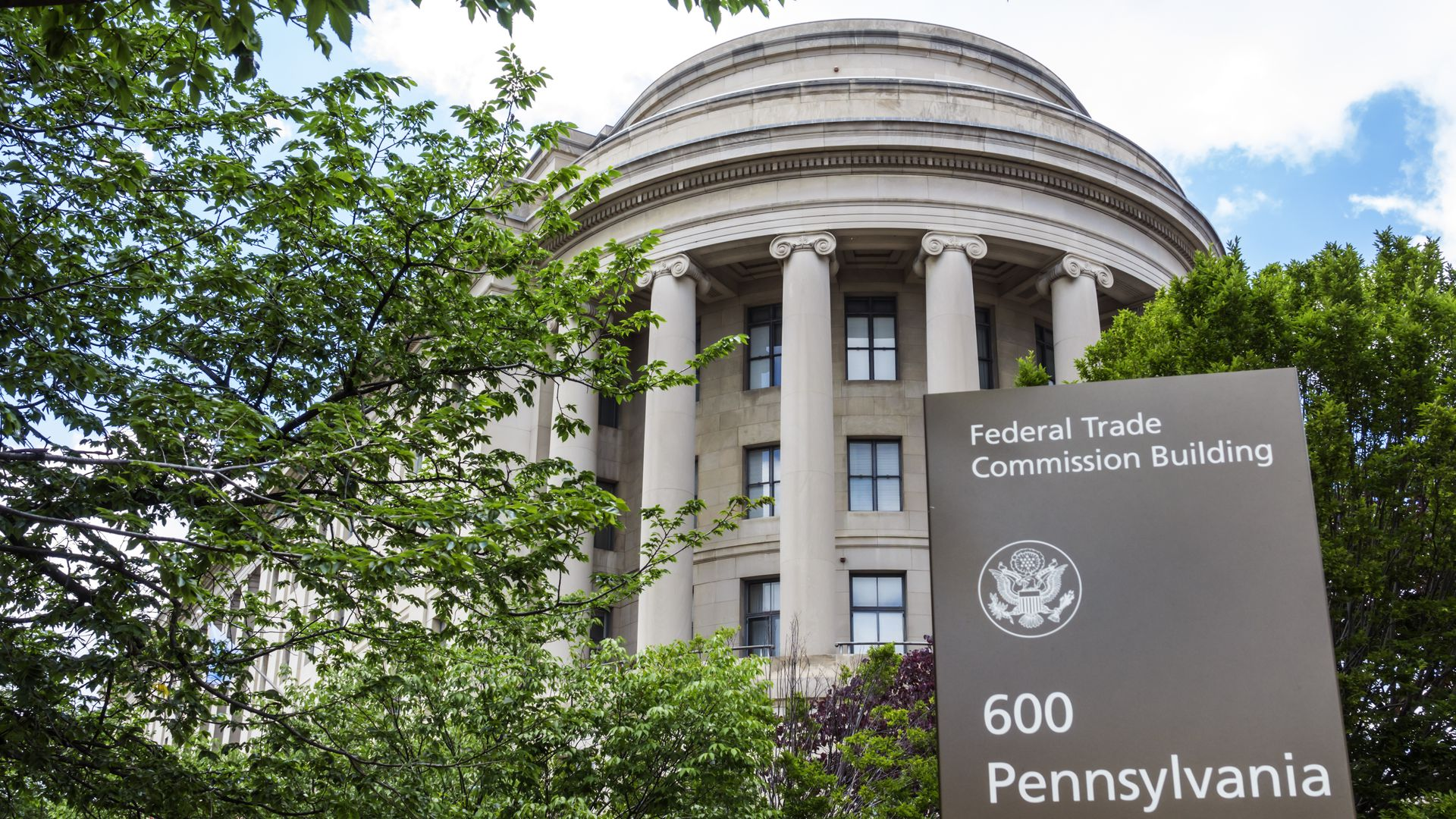 A photo of the Federal Trade Commission building with a sign out front