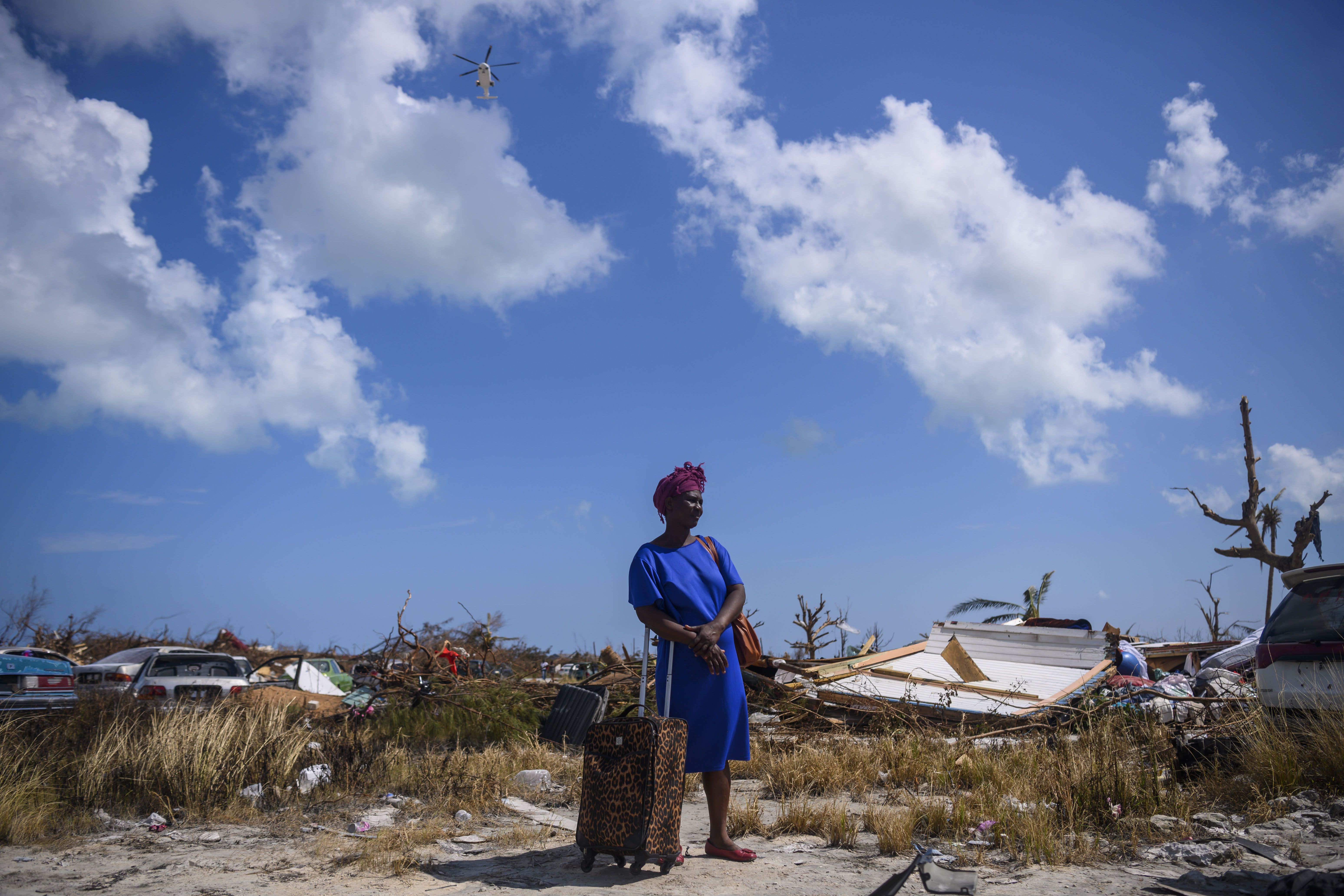 Dejani Louistan, who was displaced by Hurricane Dorian, stands with the only belongings she managed to salvage