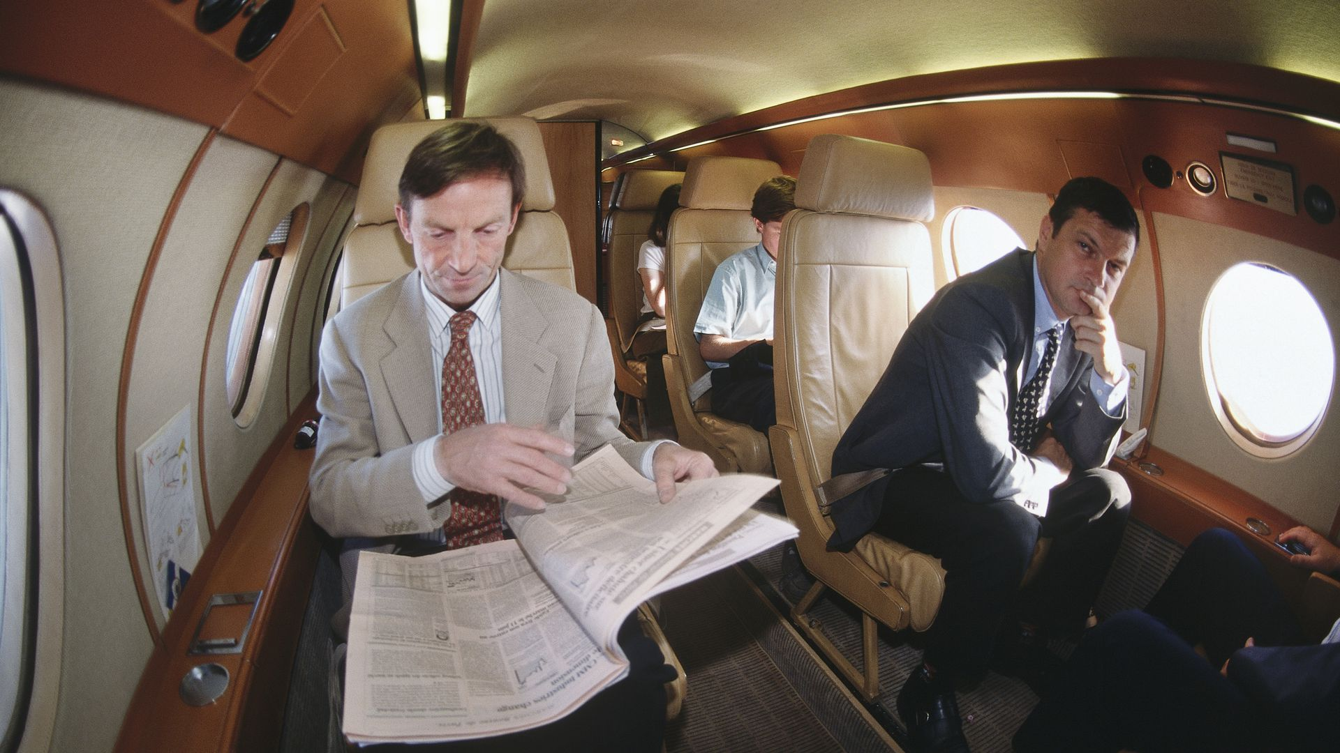 Man reading newspaper on private jet