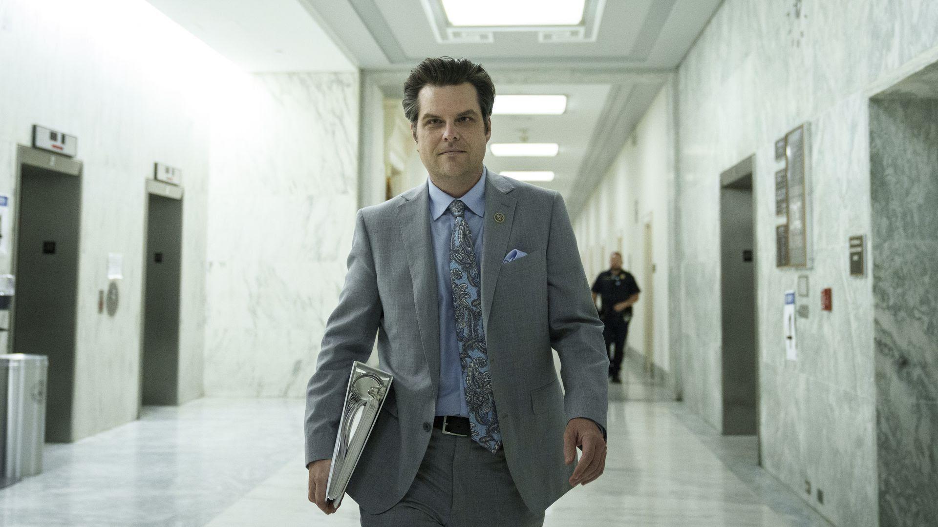 Matt Gaetz walks through a hallway on Capitol Hill with a binder in one hand.