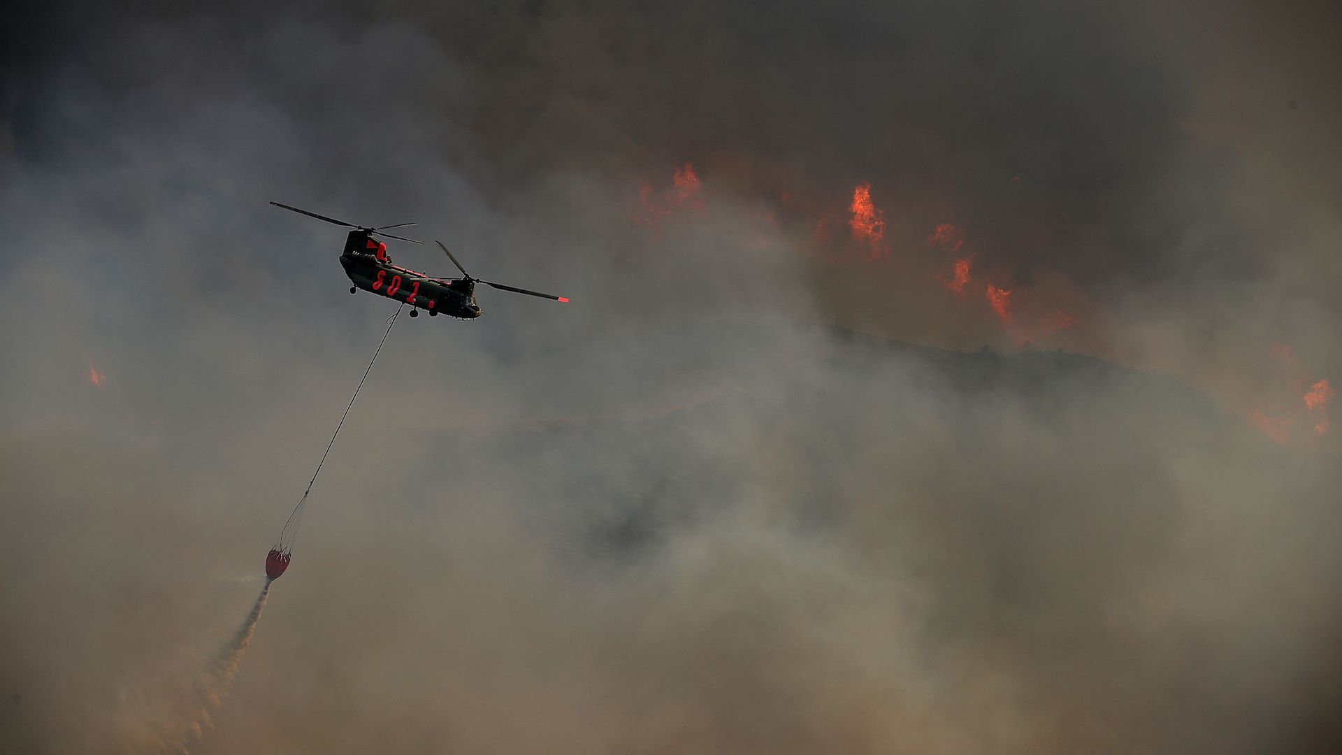 LAKEPORT, CA - JULY 31: A helicopter drops water on the River Fire as it burns through a canyon on July 31, 2018 in Lakeport, California.