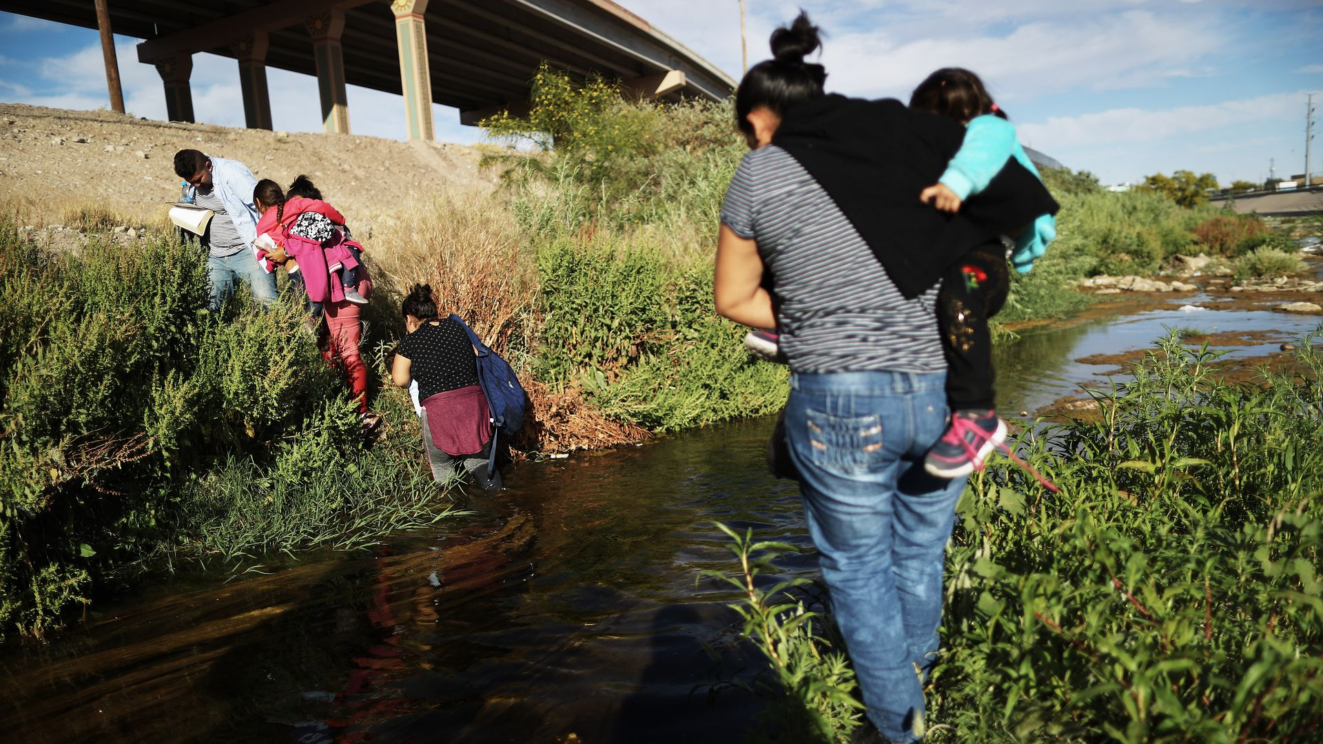 Migrants cross the border between the U.S. and Mexico at the Rio Grande river, as they walk to enter El Paso, Texas,.