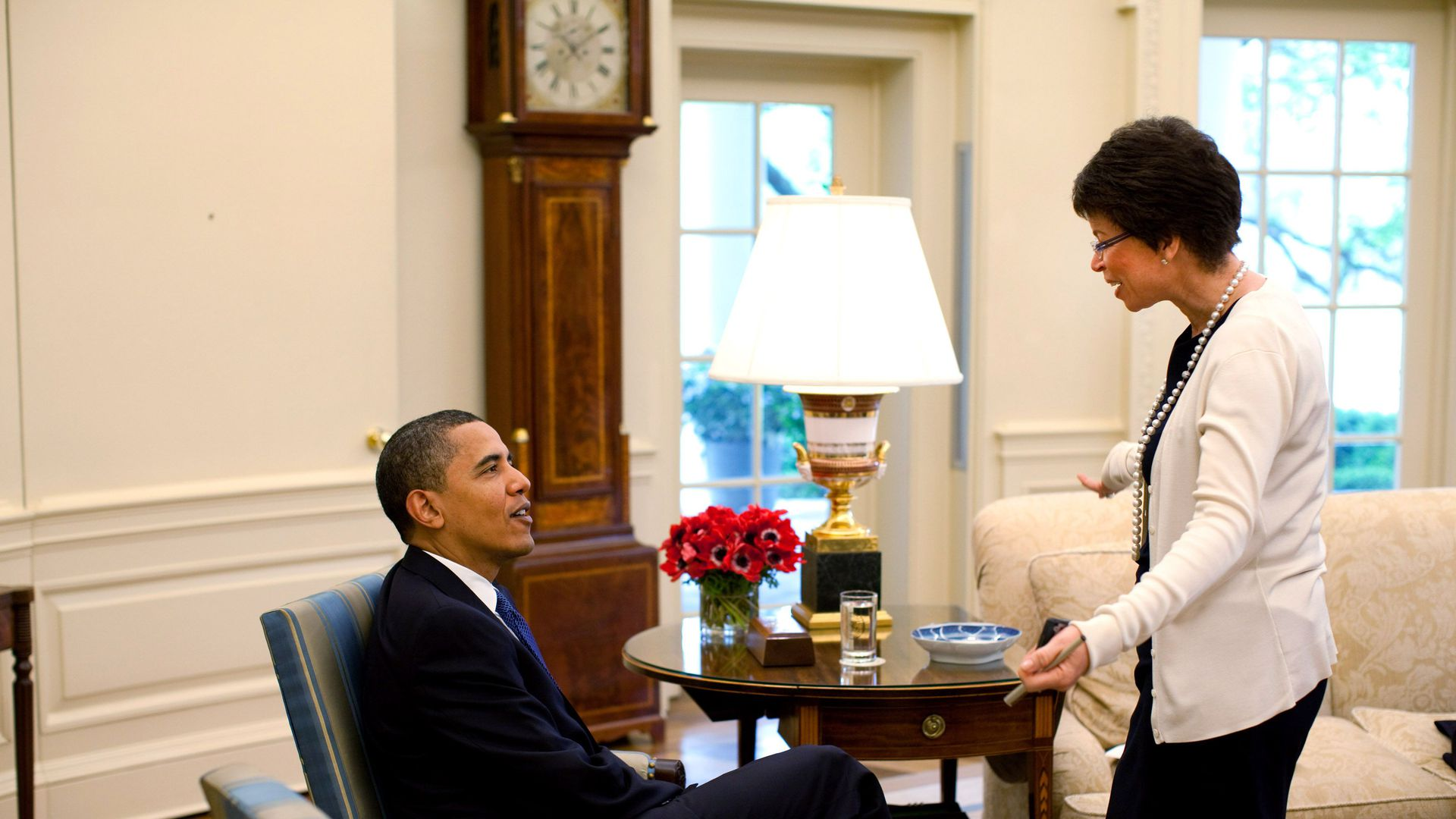 In this image, Obama is sitting on an armchair in the Oval Office while Valerie stands in a white cardigan and speaks to him.
