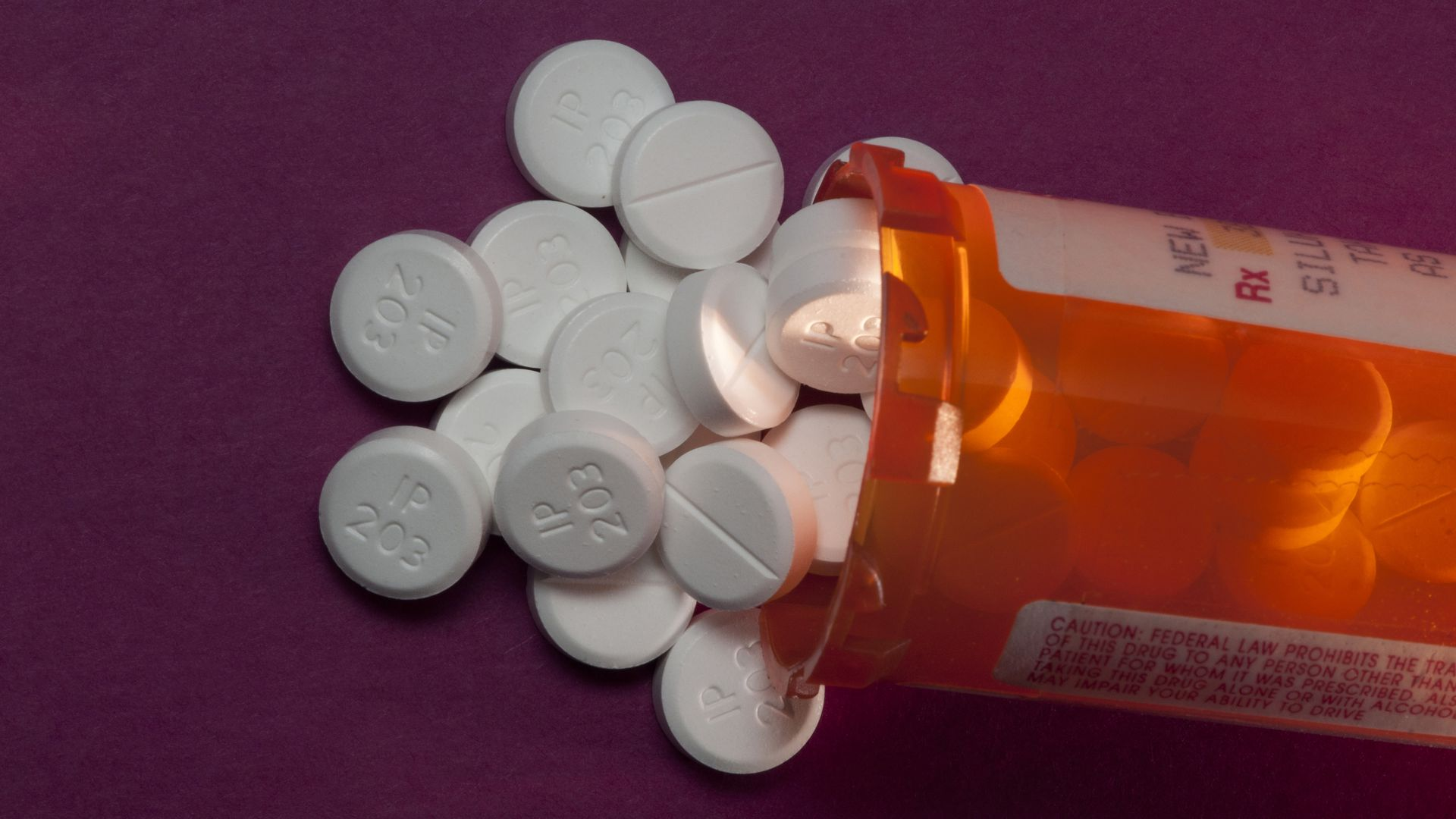 In this image, small round white oxycodone pills spill out of a prescription bottle
