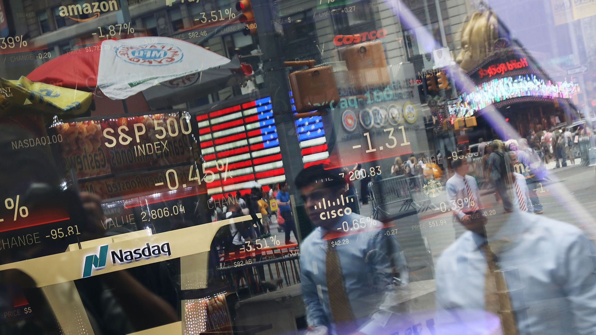 People are reflected in the window of the Nasdaq MarketSite in Times Square on July 30, 2018 in New York City