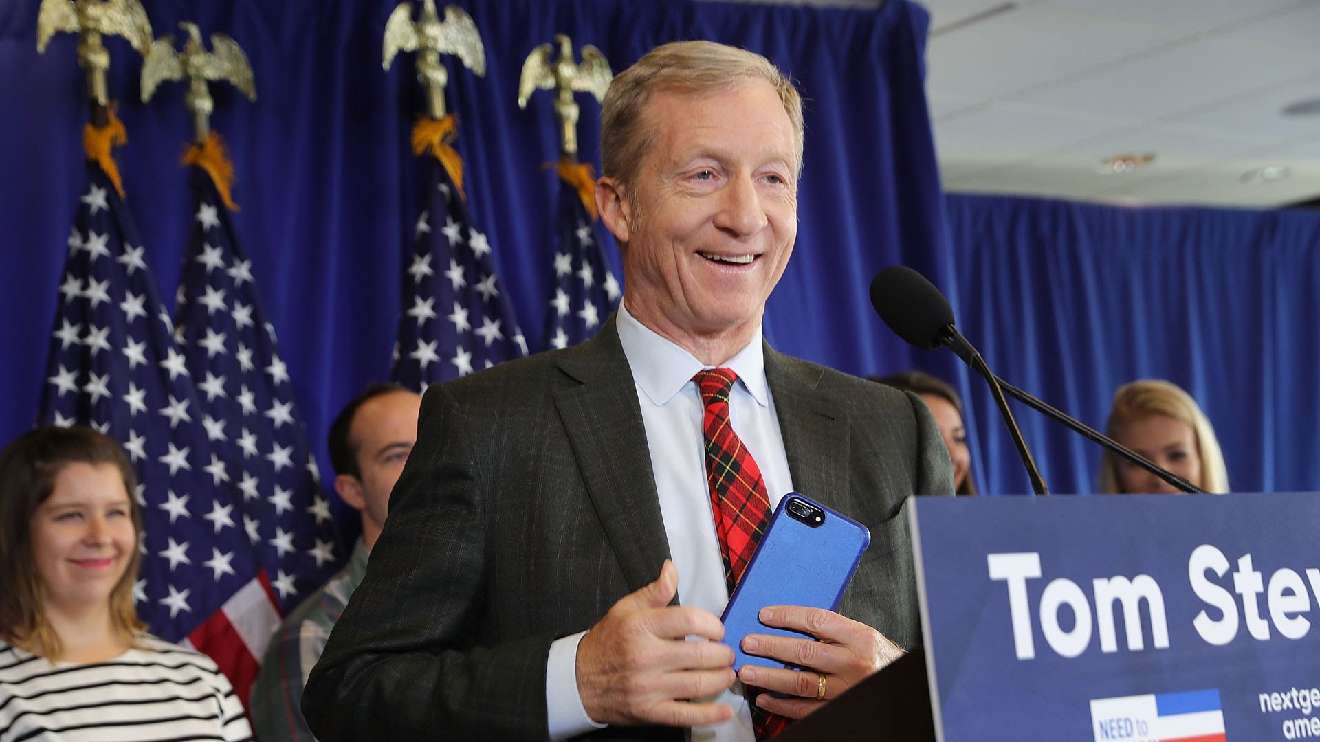 Tom Steyer smiling at a podium.
