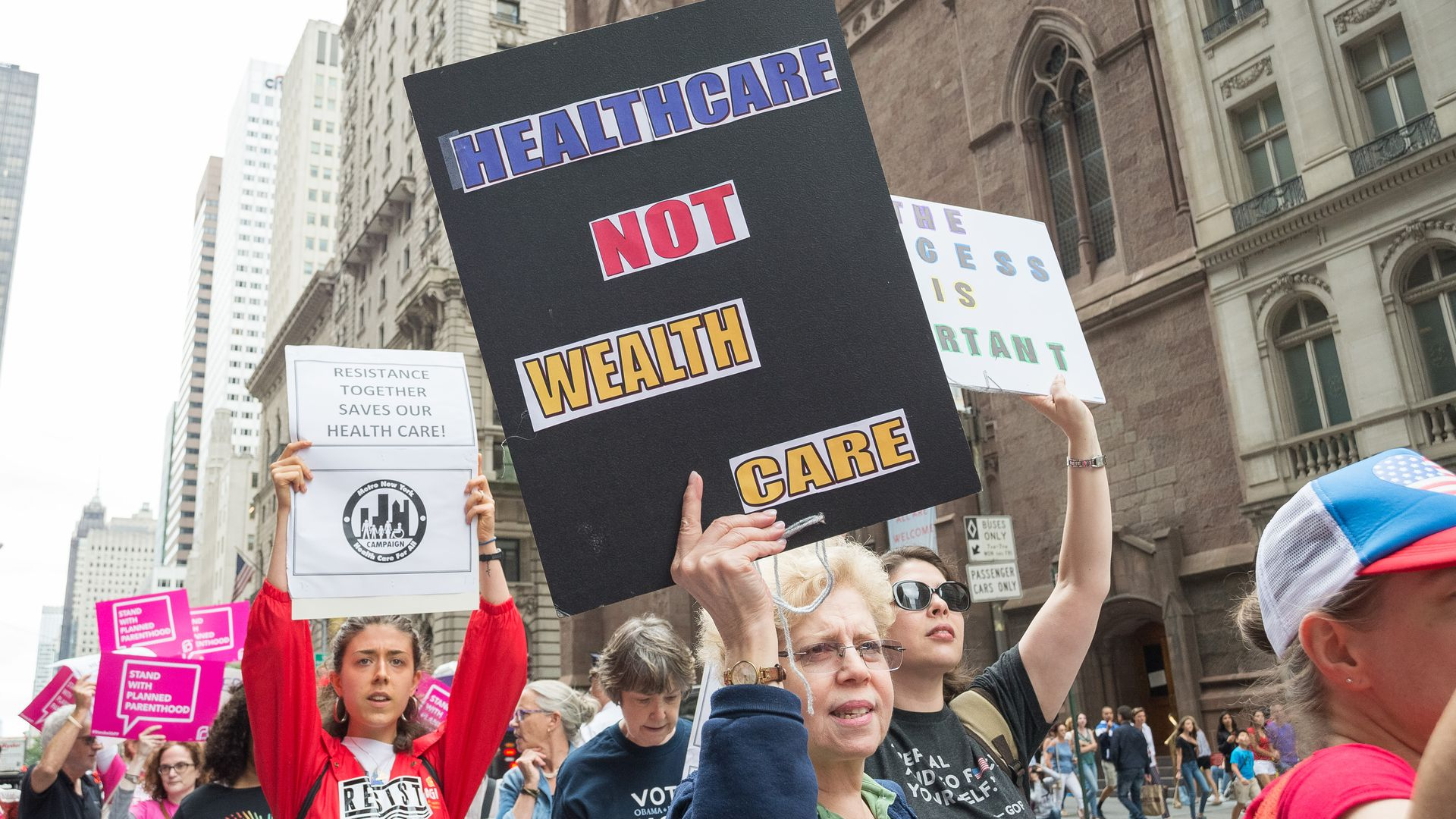 "A protestor holds a sign that says, ""Healthcare not wealthcare"""