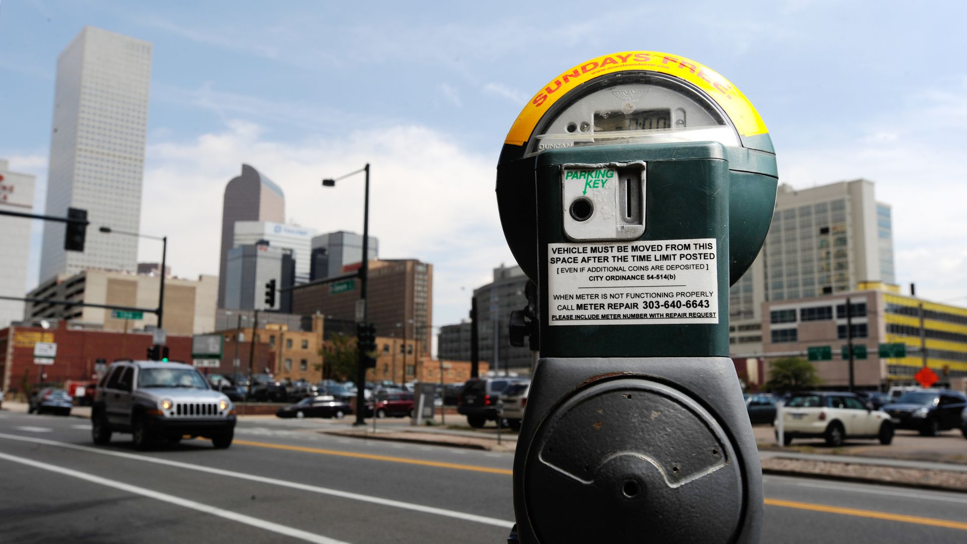 A photo of a parking meter in front of the Denver skyline