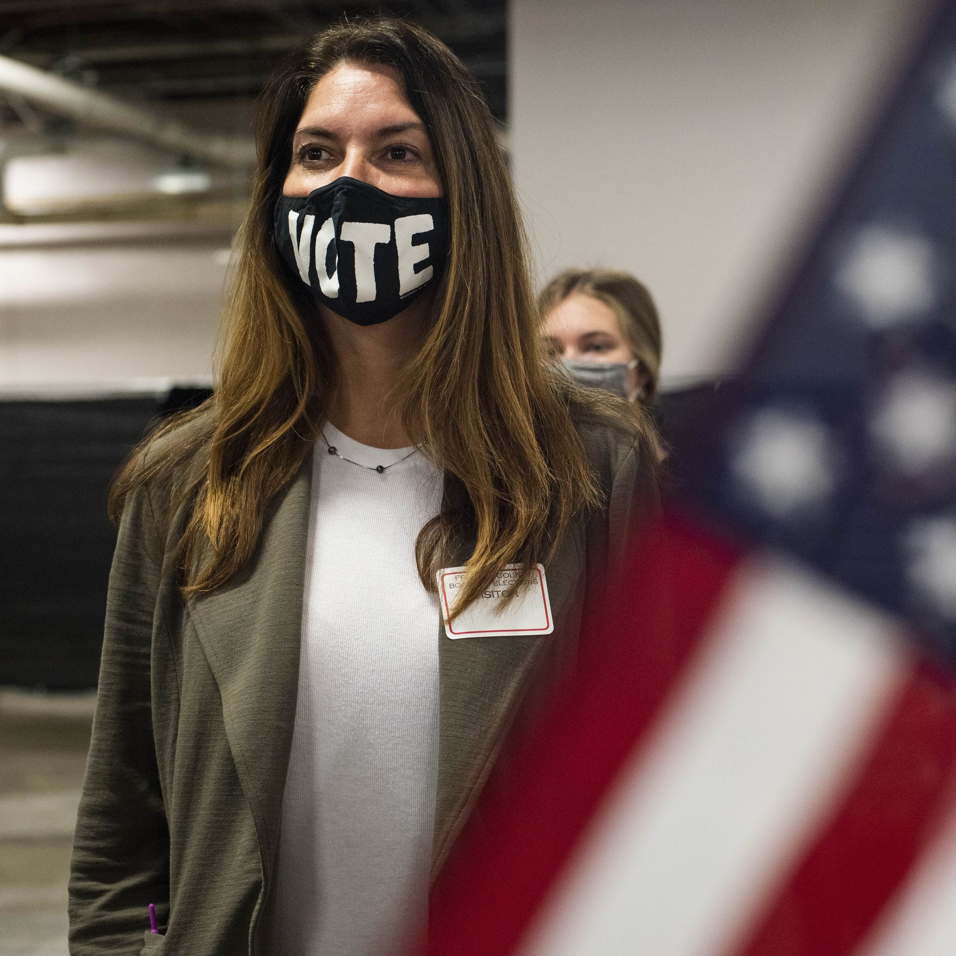 """A pollworker wears a mask reading """"VOTE"""" at a voting location."""