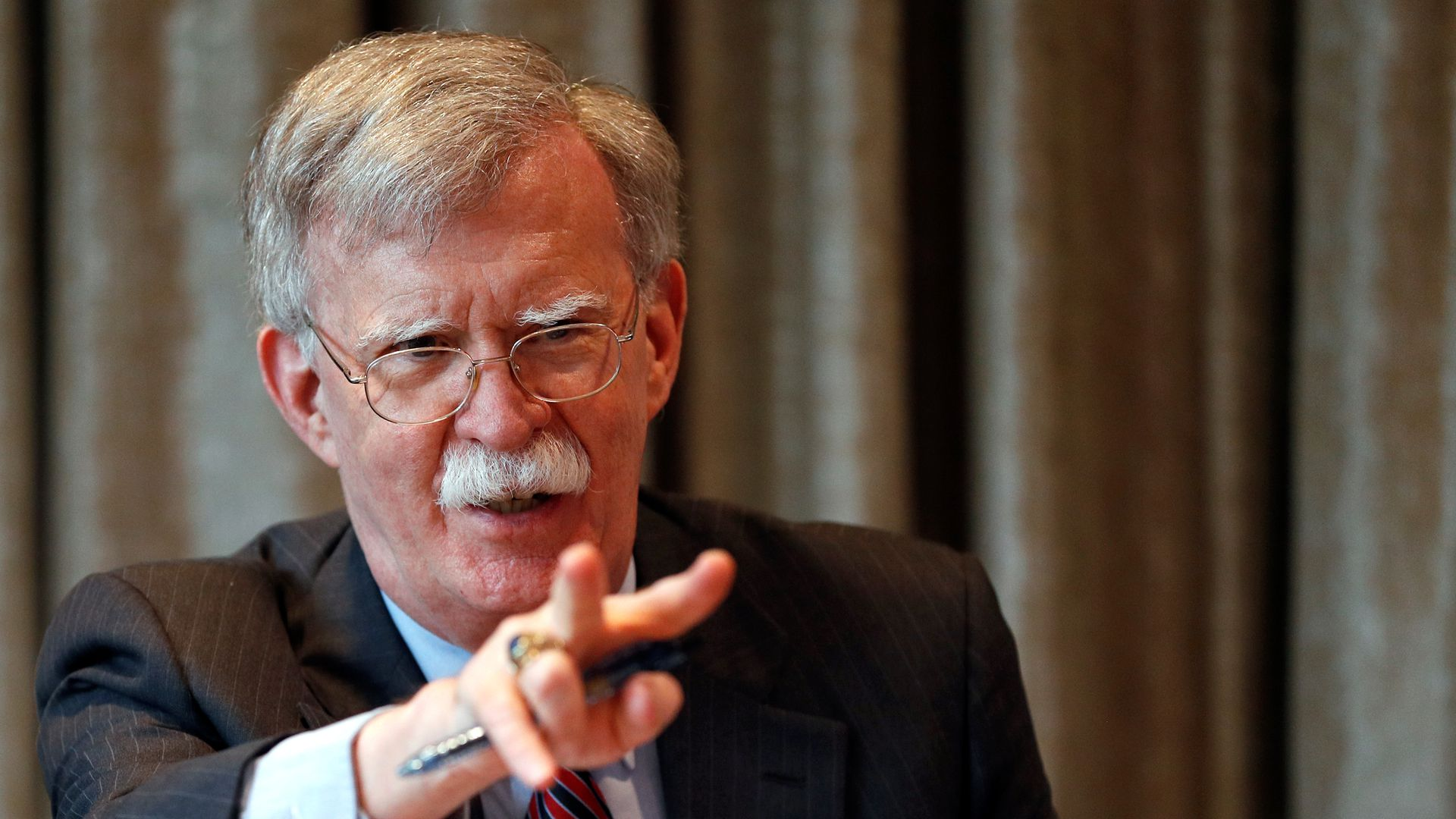 U.S. National Security Advisor, John Bolton, gestures as he meets with journalists during a visit to London