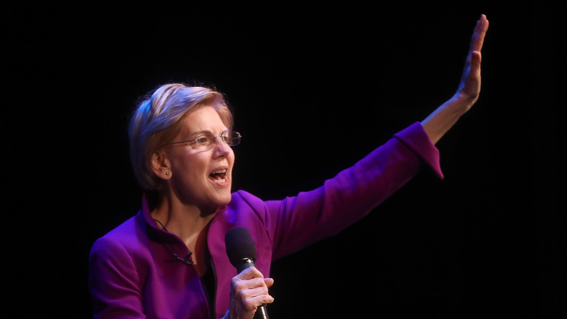 Elizabeth Warren give a speech with her arm raised up
