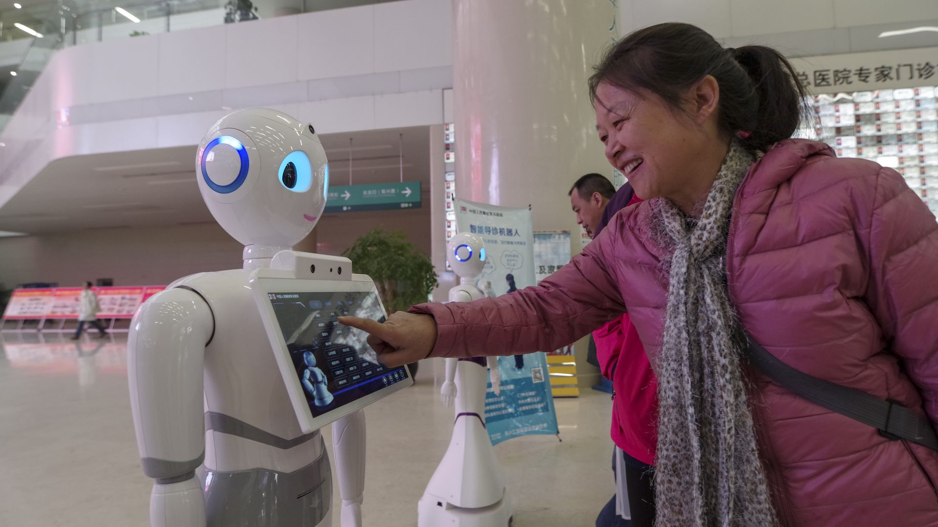 Several intelligent guide robots standing in the outpatient lobby of Beijing 301 hospital.