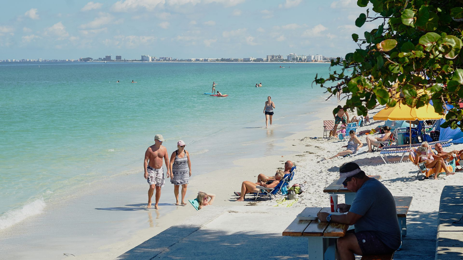 People walk along Pass-A-Grille beach in May, when beaches in Pinellas County reopened for the first time in six weeks.