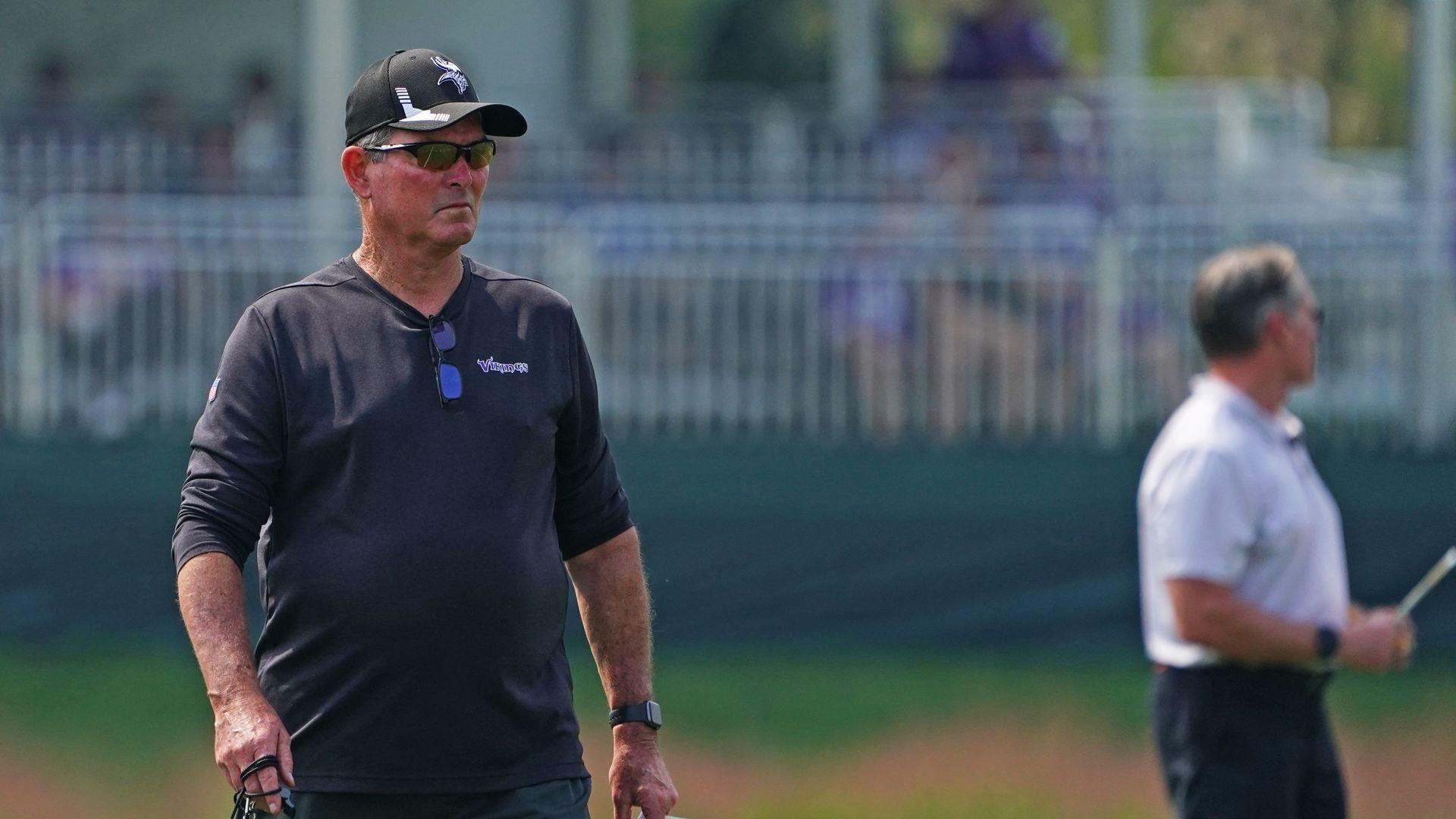 Minnesota Vikings head coach Mike Zimmer wears sunglasses while watching practice.