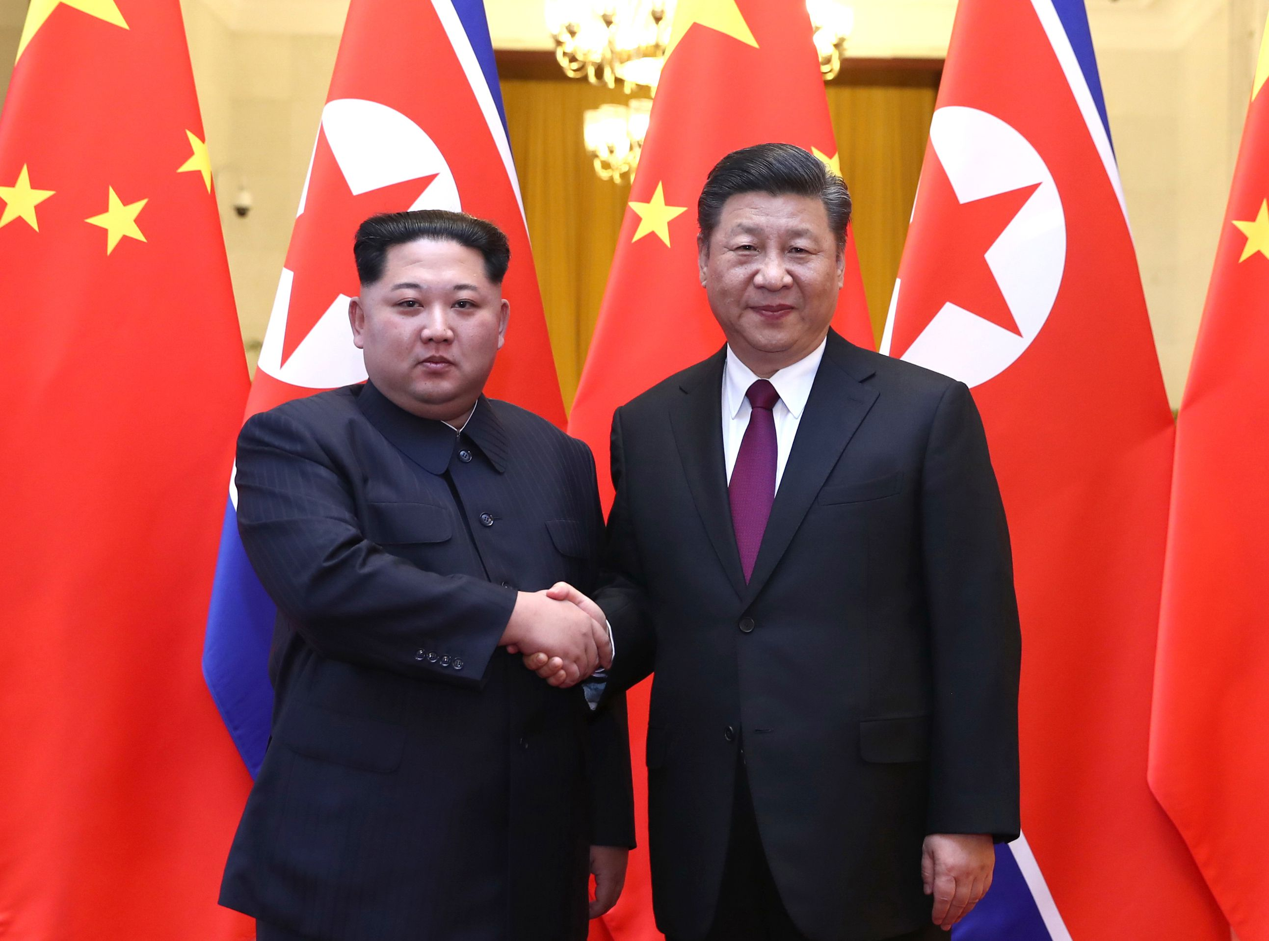 Kim Jong-un and Xi Jinping shake hands in front of red flags.