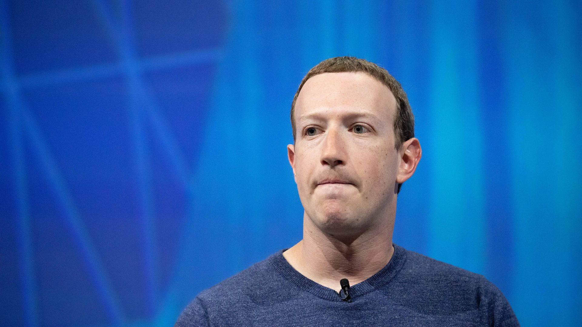 Mark Zuckerberg wearing a blue shirt before a blue background bites his lips frowning.