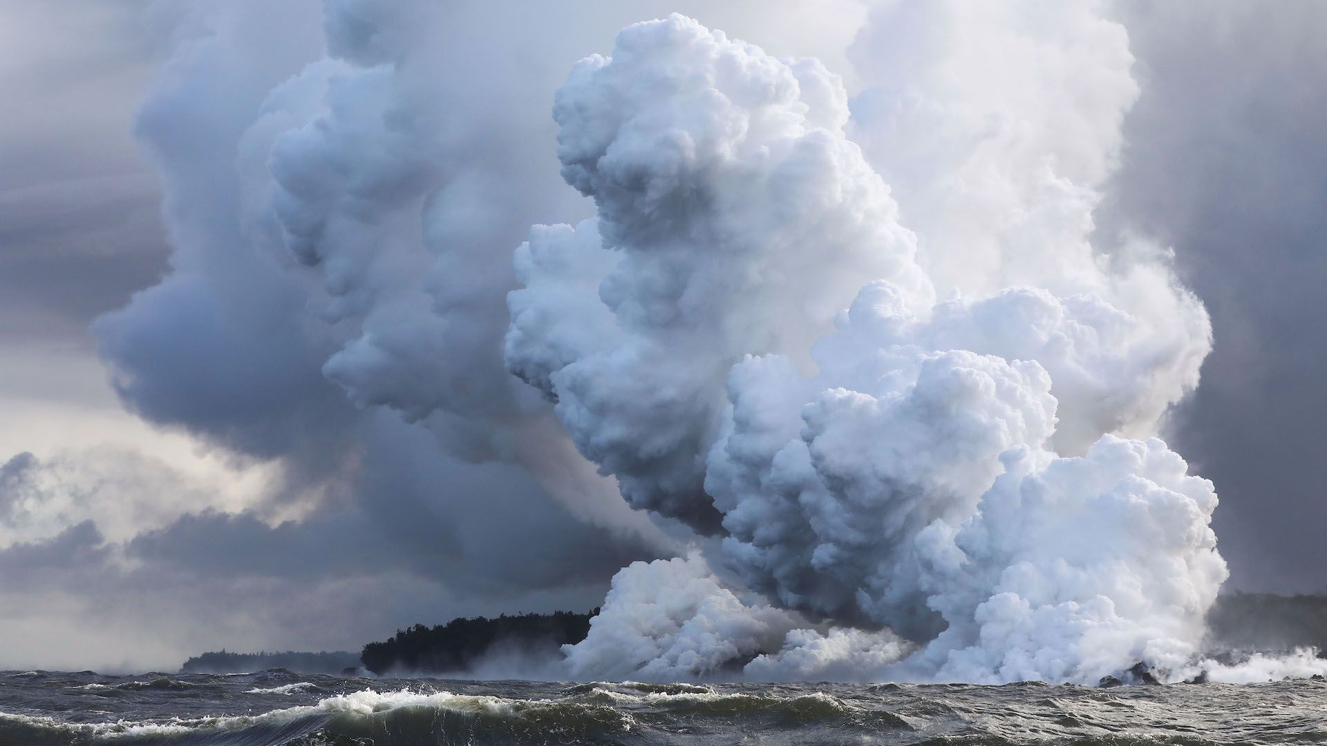 Steam plumes rise as lava enters the Pacific Ocean, after flowing to the water from a Kilauea volcano fissure, on Hawaii's Big Island on May 20, 2018 near Pahoa, Hawaii.