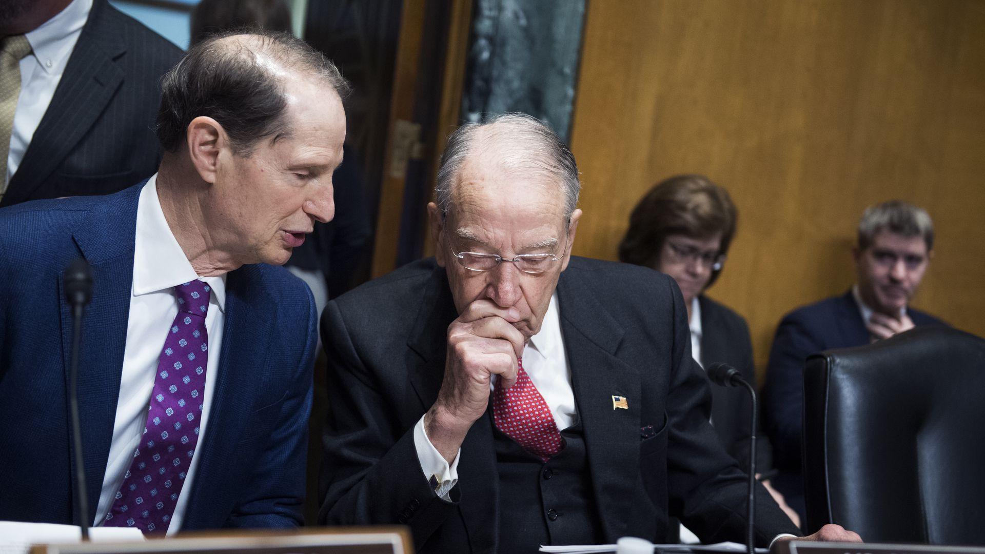 Sens. Ron Wyden and Chuck Grassley sit and talk at a hearing.
