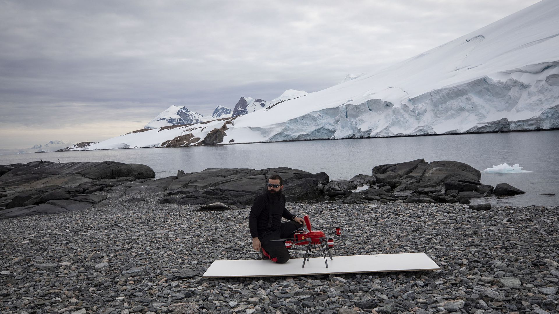 scientist sitting next to a lidar-equipped drone outdoors in Antarctica