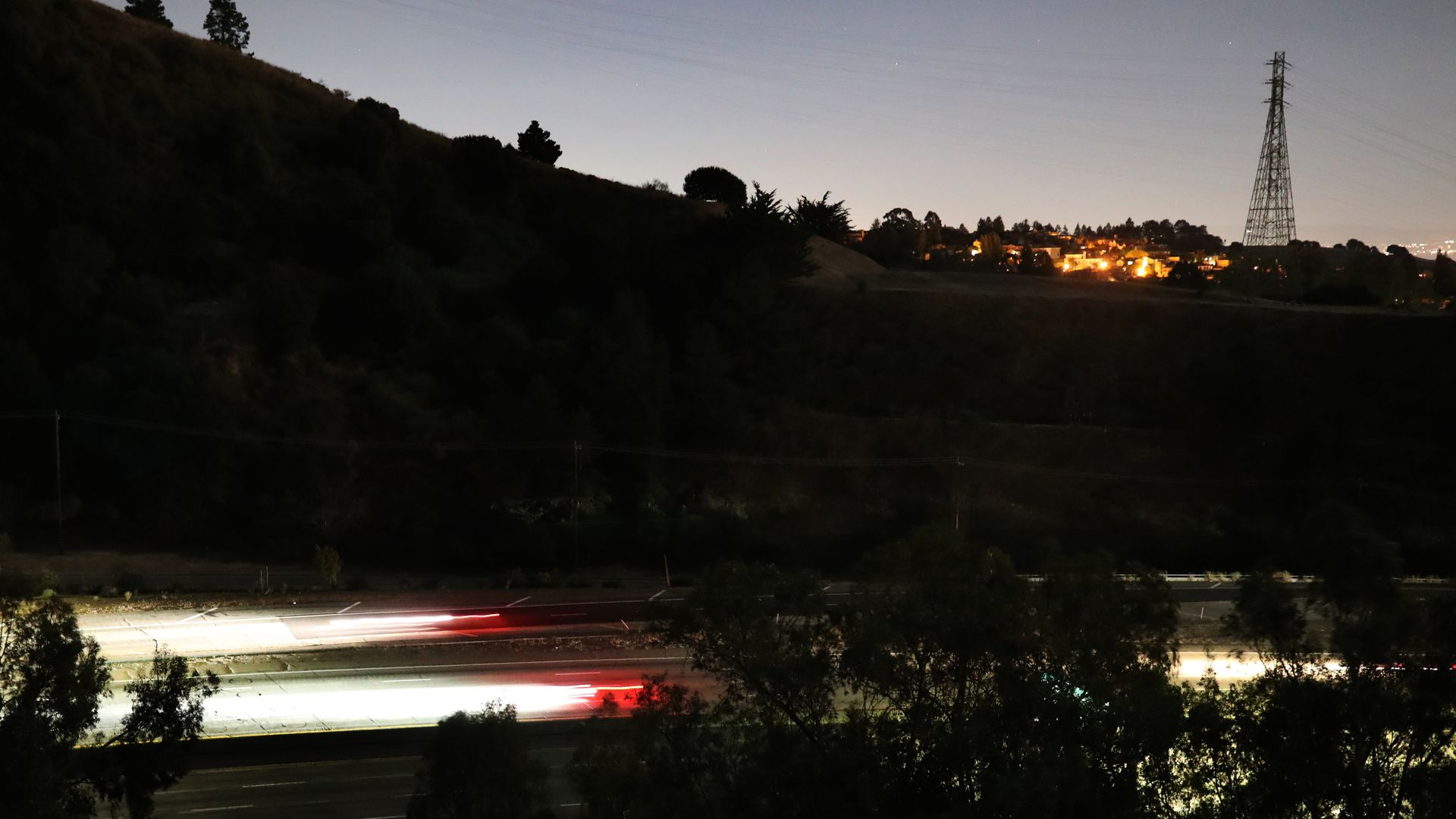 Streaks of lights from vehicles drive along highway 24 during the PG&E power outage in Oakland, Calif