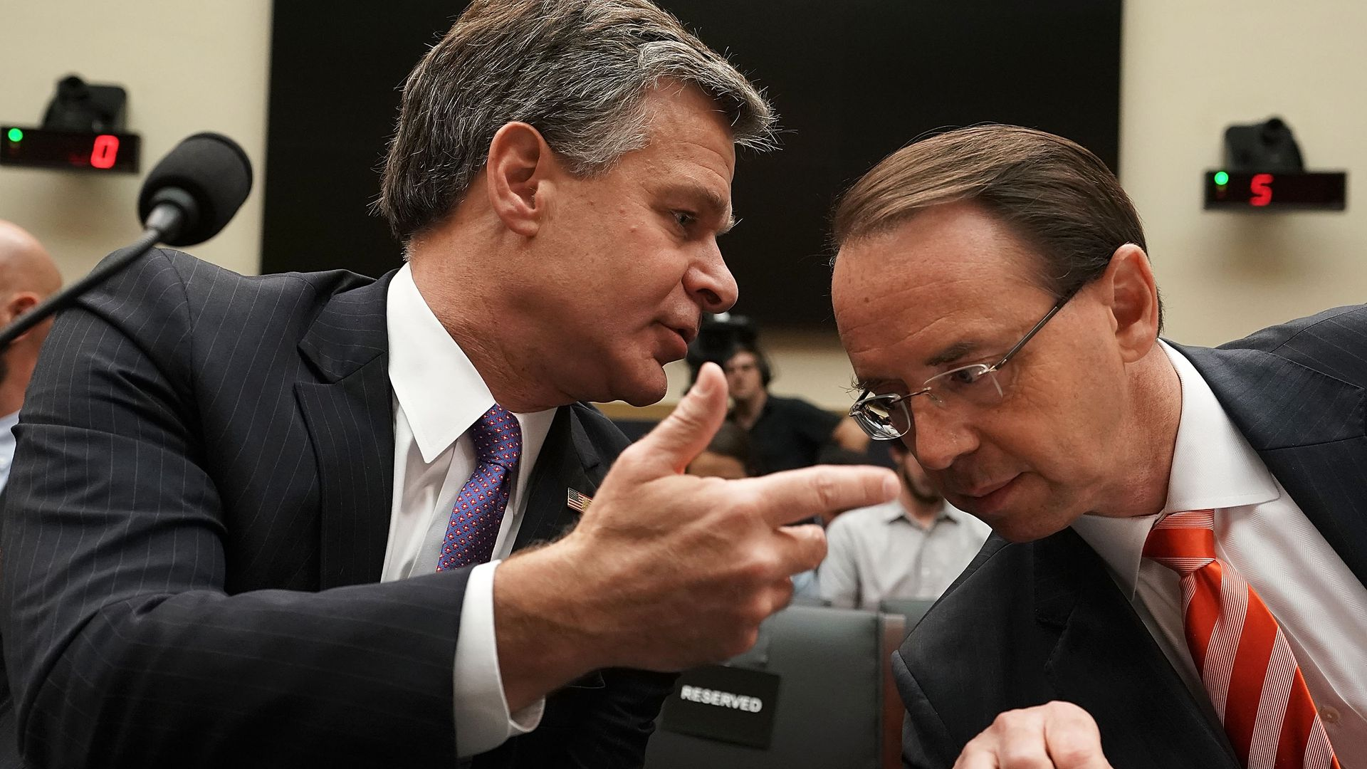 FBI director Christopher Wray leaning over to talk to Rod Rosenstein